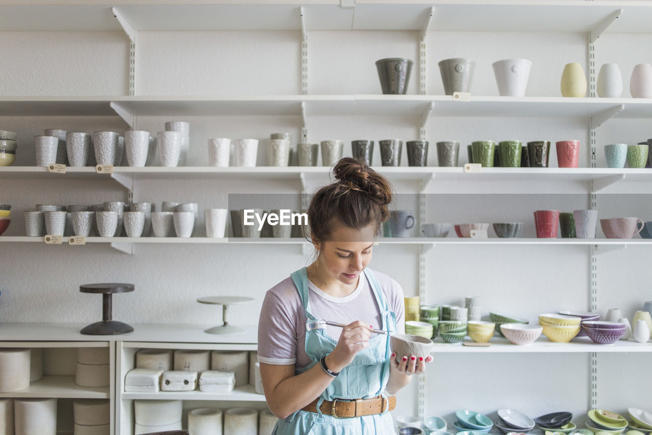 shelf, one person, indoors, waist up, lifestyles, real people, casual clothing, looking down, looking, front view, standing, holding, childhood, kitchen, women, child, domestic room, container, hairstyle, innocence