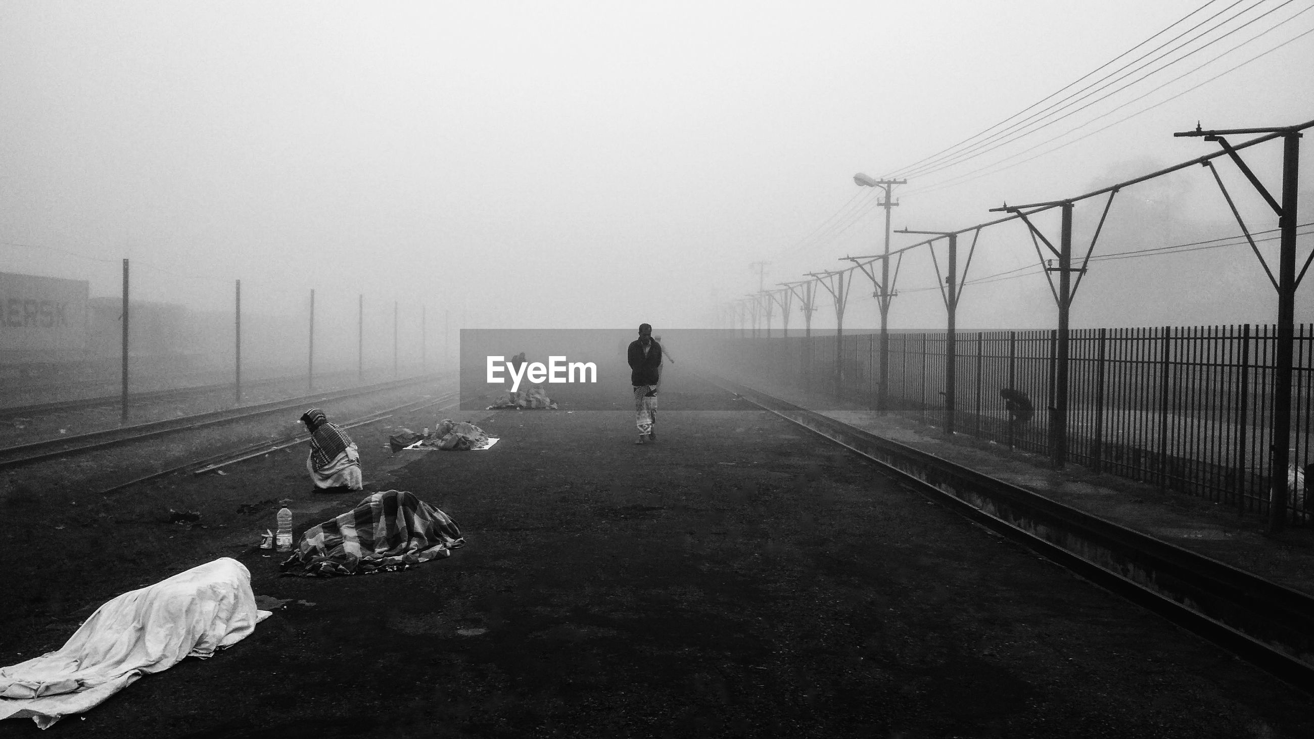People on empty footpath during foggy weather