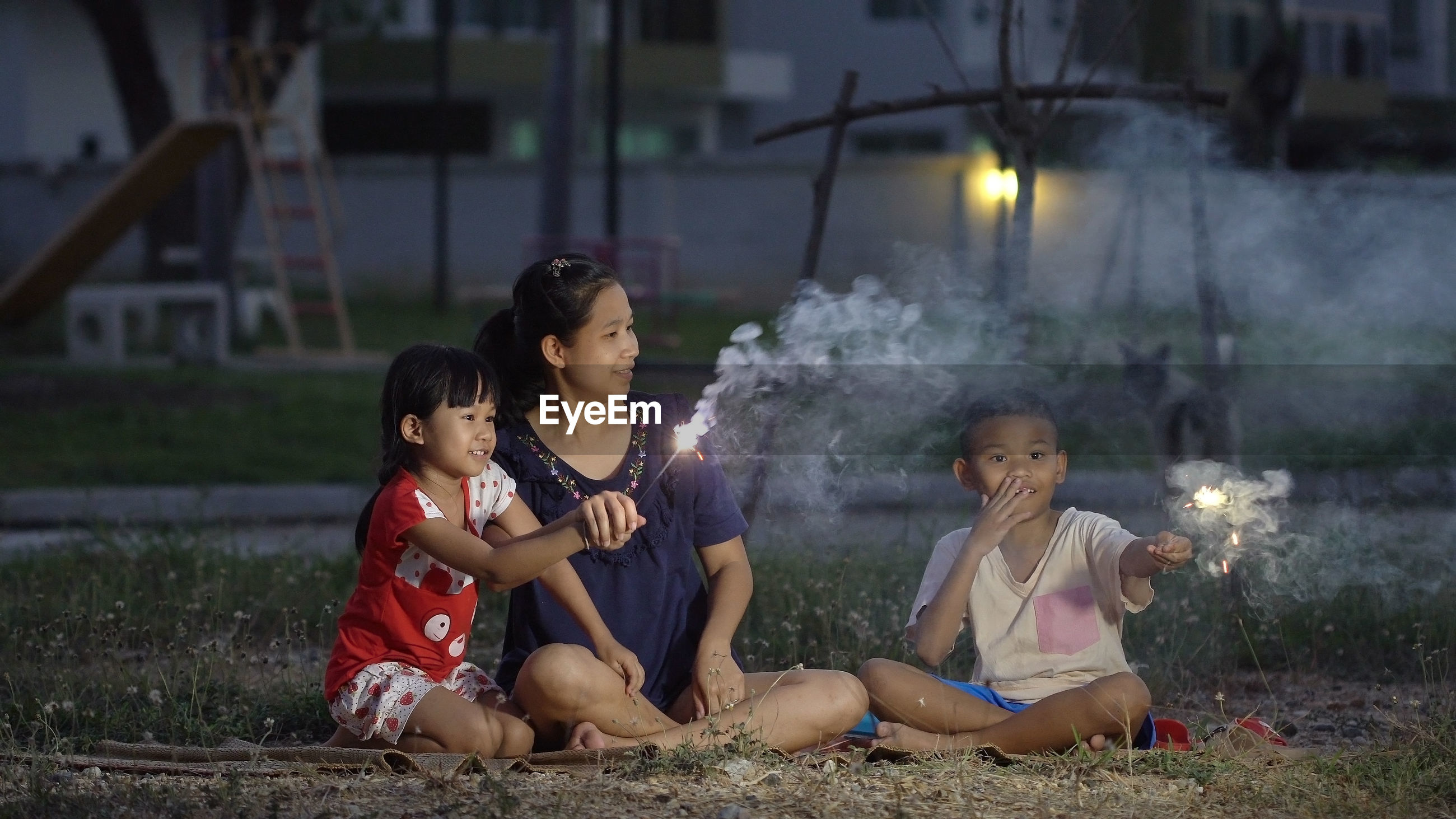 Mother sitting with son and daughter holding sparklers at night