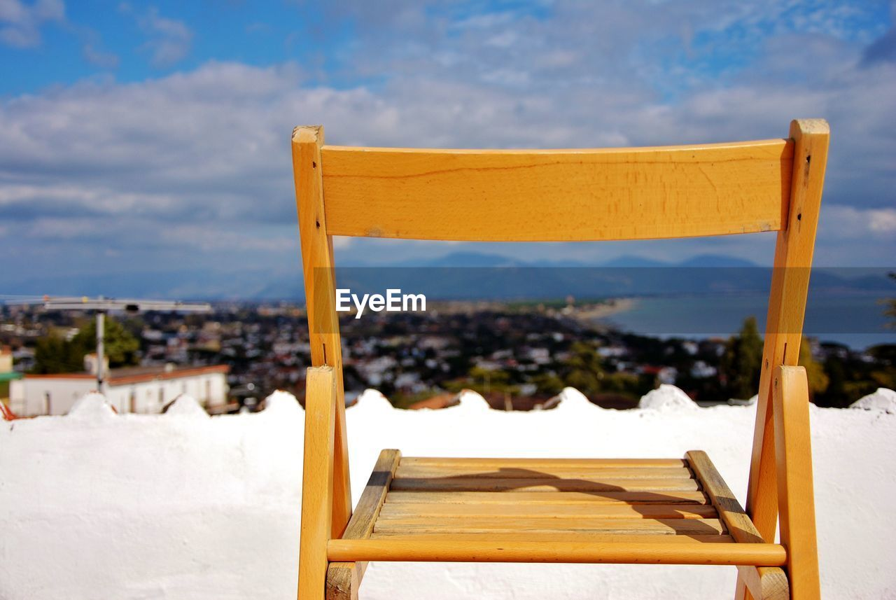 WOODEN CHAIR ON SNOW COVERED LAND