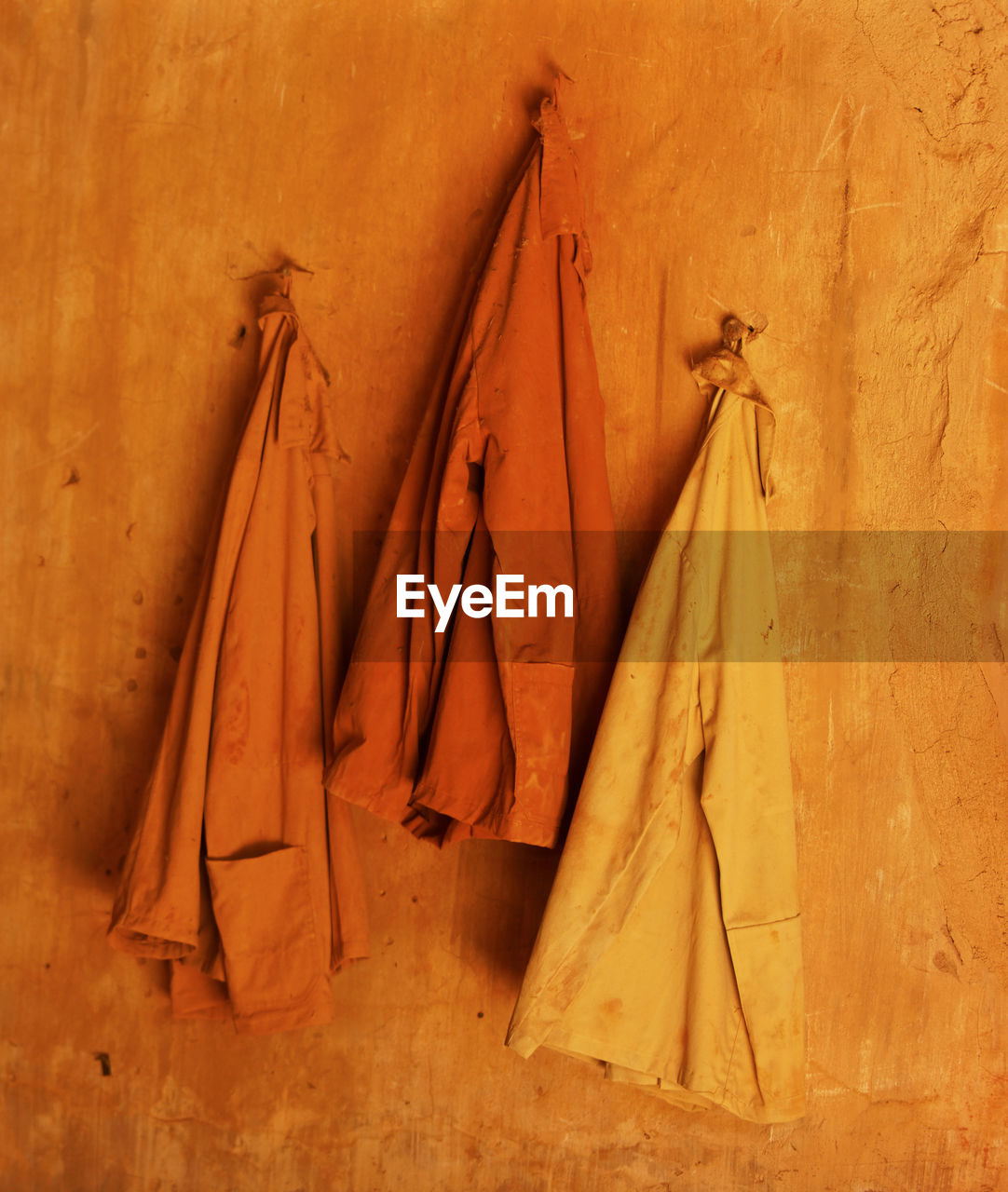 clothing, no people, hanging, indoors, coathanger, coat, wall - building feature, group of objects, wood - material, variation, still life, architecture, group, wall, choice, jacket, medium group of objects, in a row, bag, clean