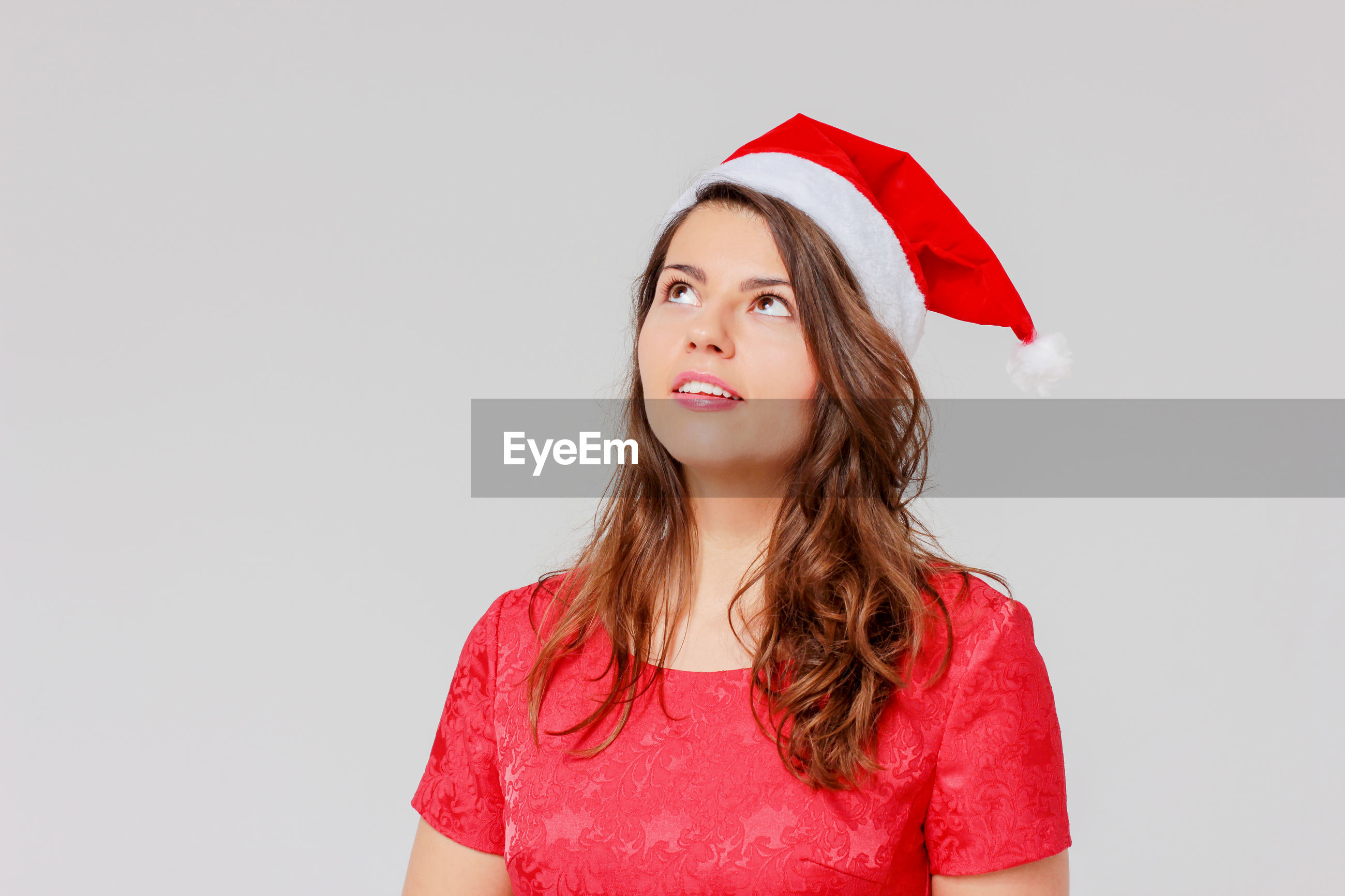 Thoughtful young woman wearing santa hat while standing against gray background