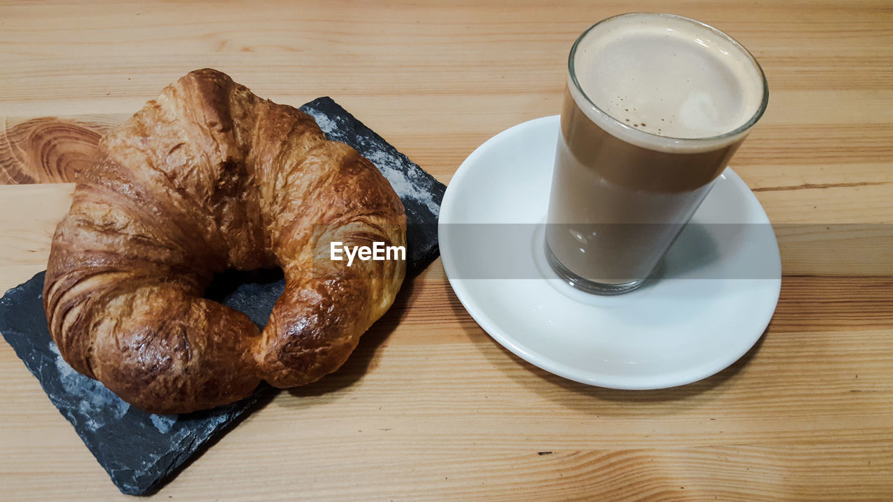 drink, food and drink, refreshment, table, coffee, coffee - drink, cup, mug, baked, coffee cup, food, croissant, freshness, still life, bread, breakfast, indoors, french food, wood - material, high angle view, meal, no people, crockery, frothy drink, glass, snack, temptation