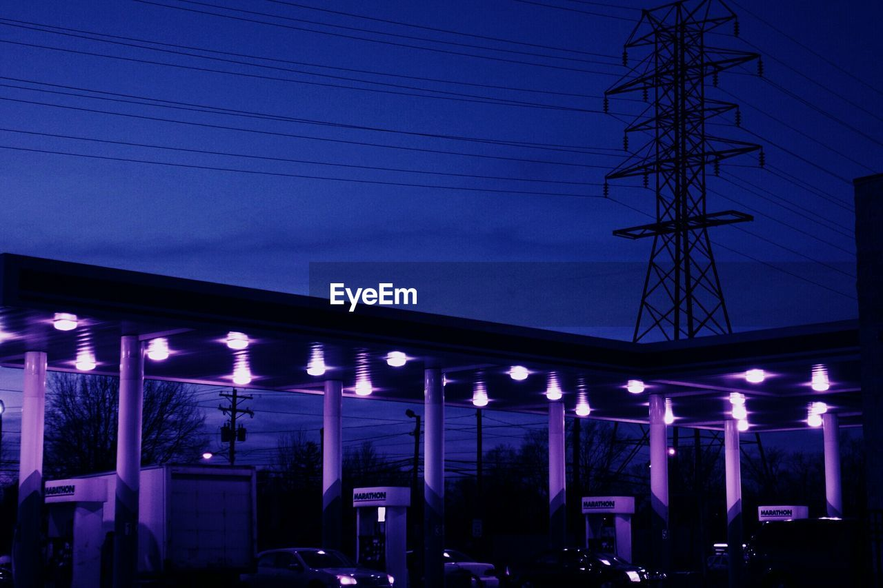 Illuminated toll booth against silhouette electricity pylon against sky