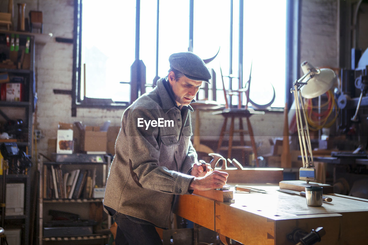 indoors, one person, workshop, real people, occupation, concentration, small business, young adult, table, workbench, working, casual clothing, art and craft, window, holding, three quarter length, day, craft, business, skill, electric lamp