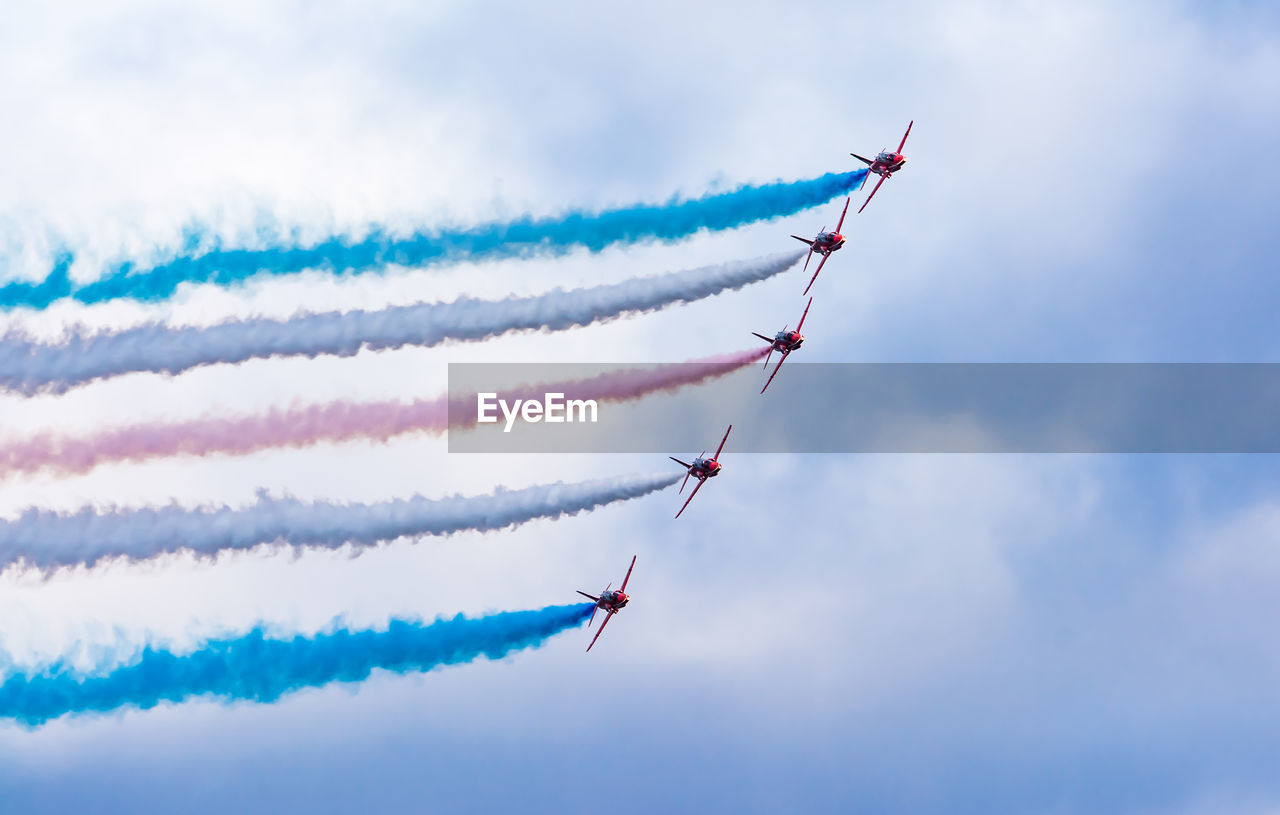 Low Angle View Of Fighter Plane Performing Smoking Stunt Against Cloudy Sky