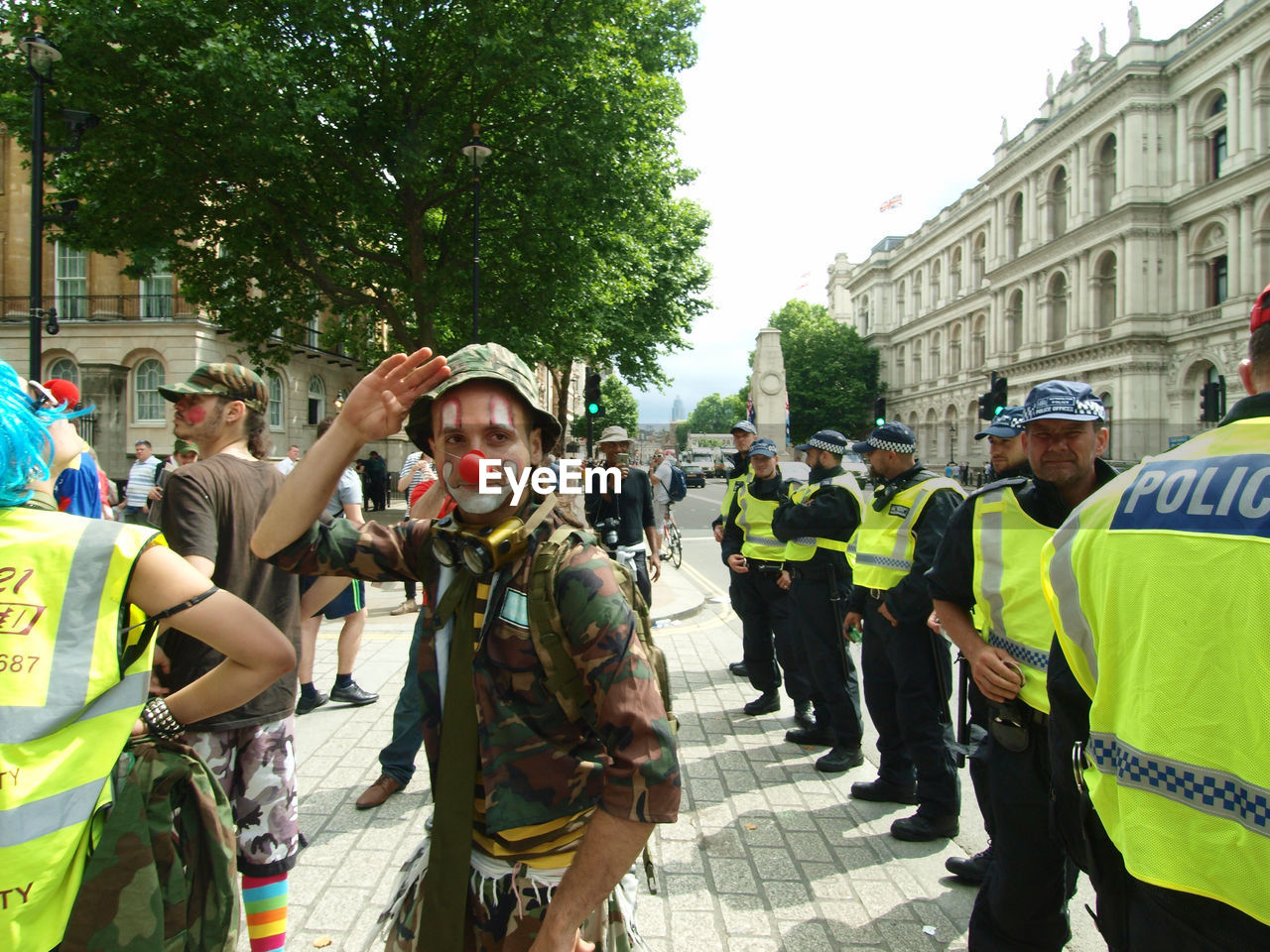 large group of people, real people, men, building exterior, built structure, day, architecture, standing, military uniform, police uniform, togetherness, tree, outdoors, women, protestor, city, riot, adult, people