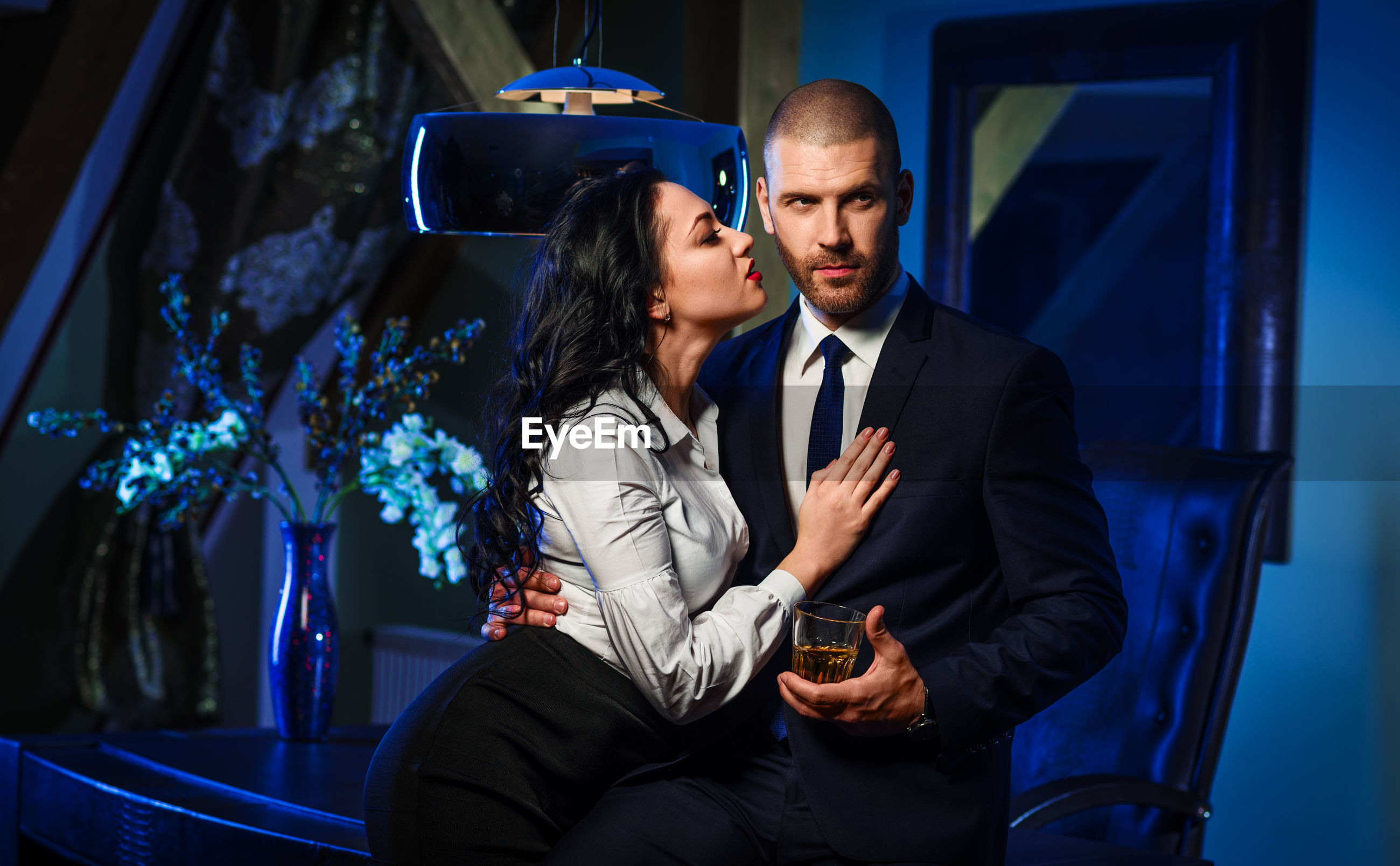 Businessman holding alcohol while standing with romantic woman in office