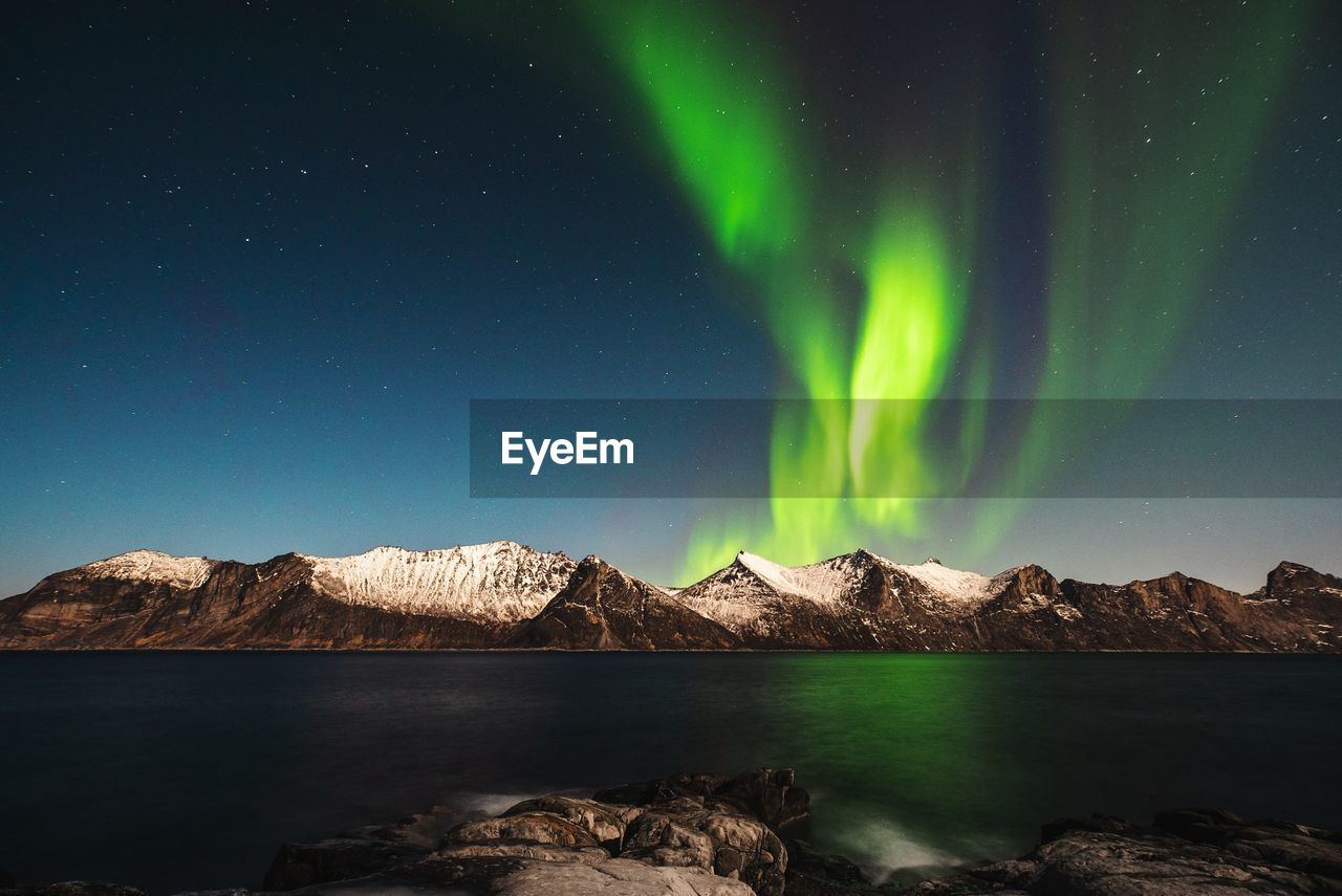 Scenic View Of Sea And Snowcapped Mountains Against Aurora Borealis At Night
