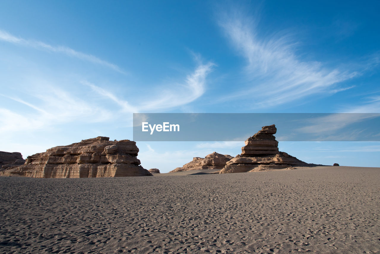 sky, rock, beauty in nature, rock formation, solid, cloud - sky, land, tranquility, scenics - nature, rock - object, sand, nature, tranquil scene, non-urban scene, climate, environment, desert, no people, physical geography, arid climate, outdoors, eroded