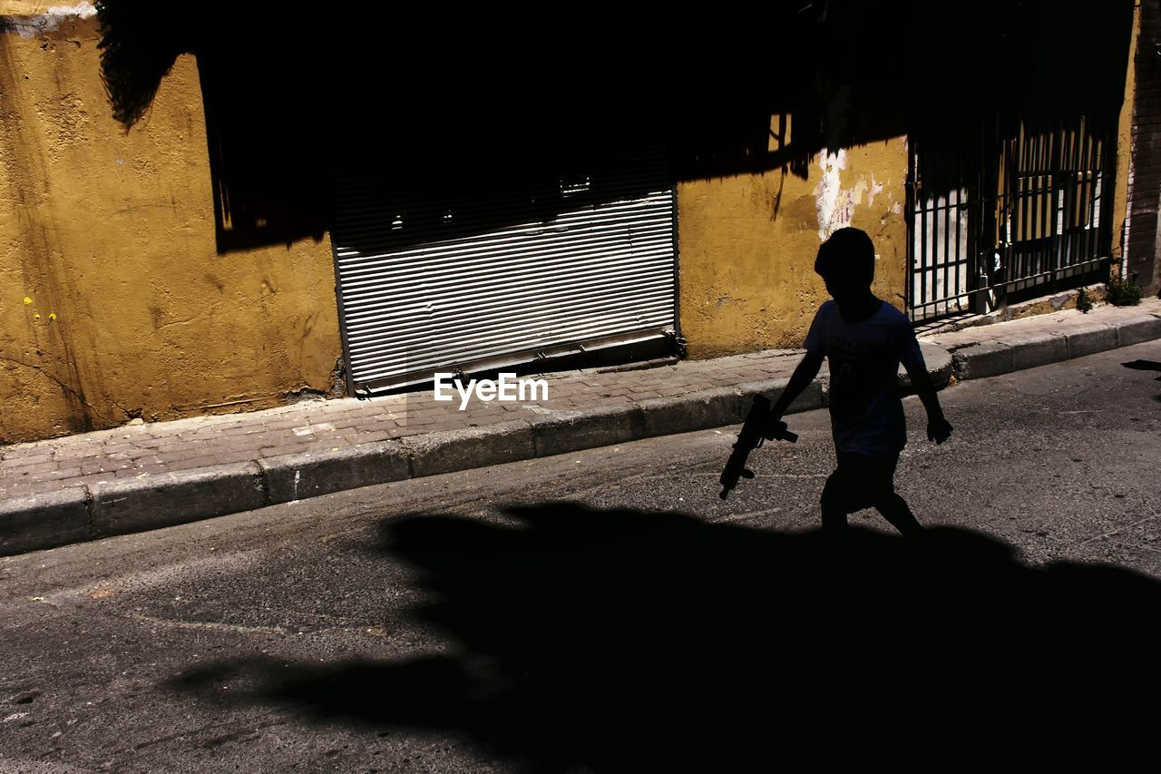 Silhouette Boy With Toy Gun Walking On Road During Sunny Day
