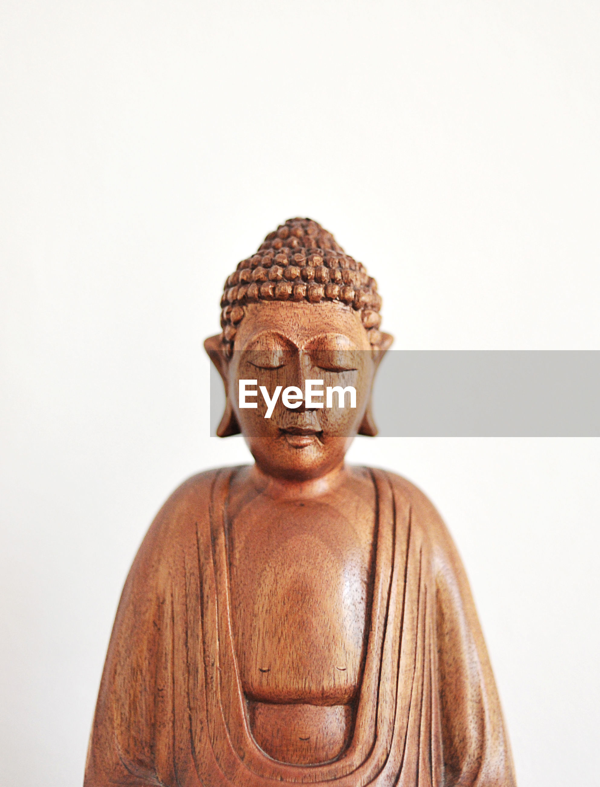 Wooden buddha sculpture against white background