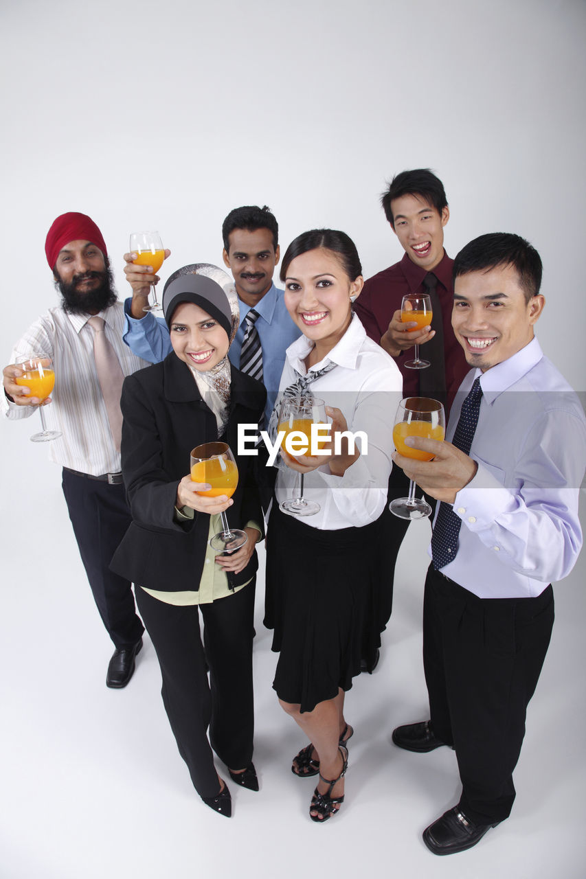 Smiling Colleagues Holding Orange Juice Glasses Against White Background