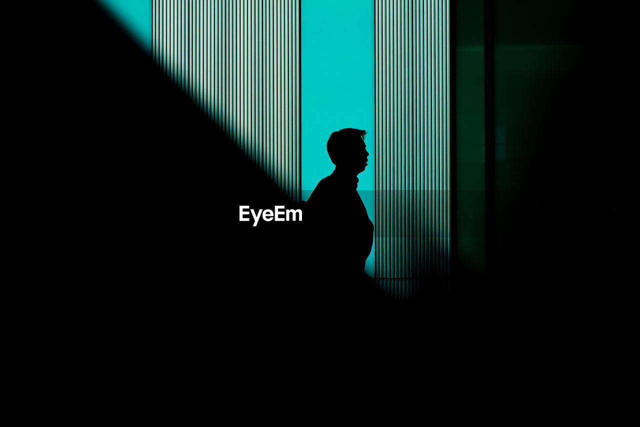 Side view of silhouette man standing against lined shadow blue green wall