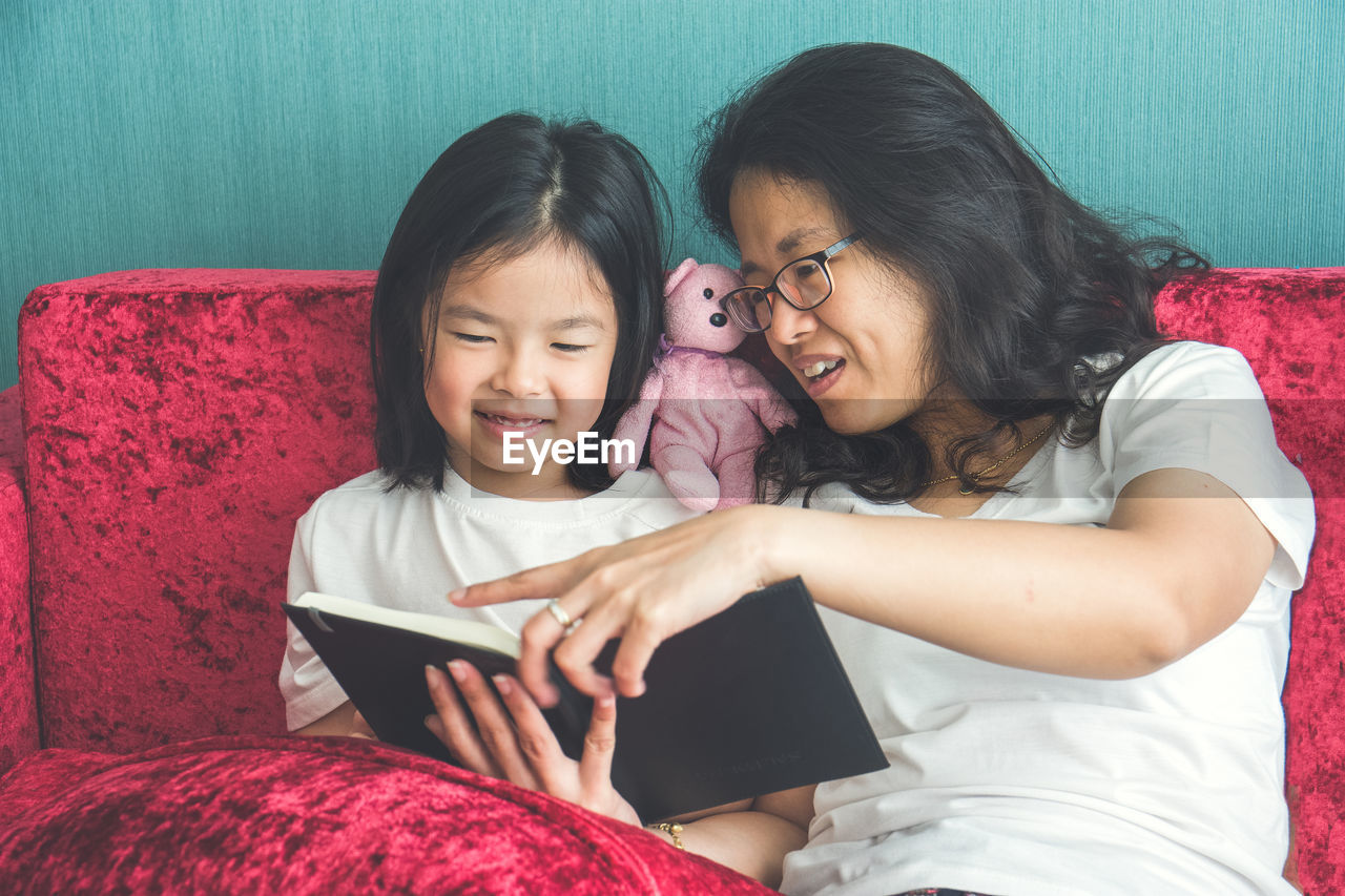 females, women, child, digital tablet, two people, togetherness, childhood, family, bonding, girls, connection, wireless technology, real people, happiness, technology, emotion, furniture, adult, positive emotion, indoors, innocence, daughter