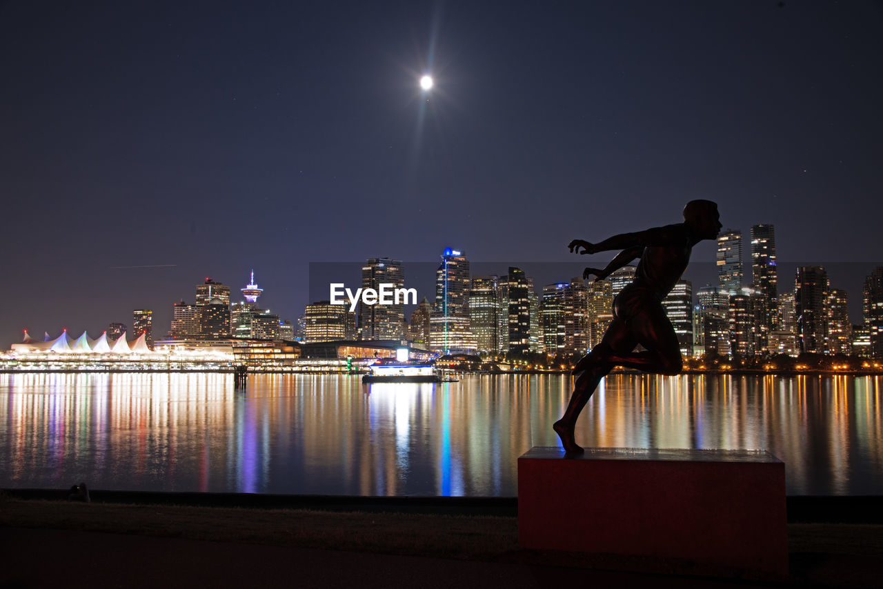 night, illuminated, city, water, sky, architecture, building exterior, built structure, nature, real people, reflection, moon, river, clear sky, lifestyles, city life, skyscraper, one person, building, cityscape, office building exterior, outdoors, modern, moonlight