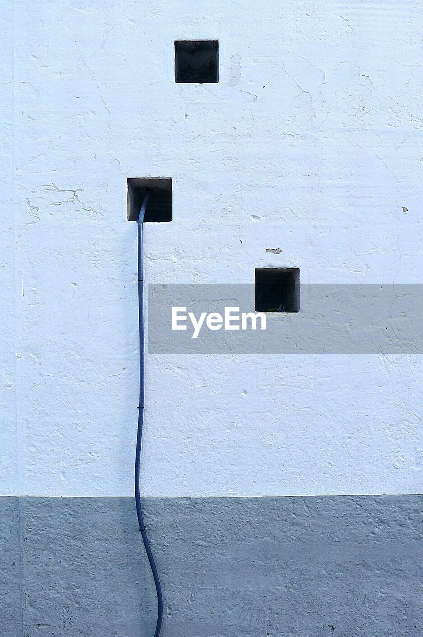 Cable Hanging From White Wall