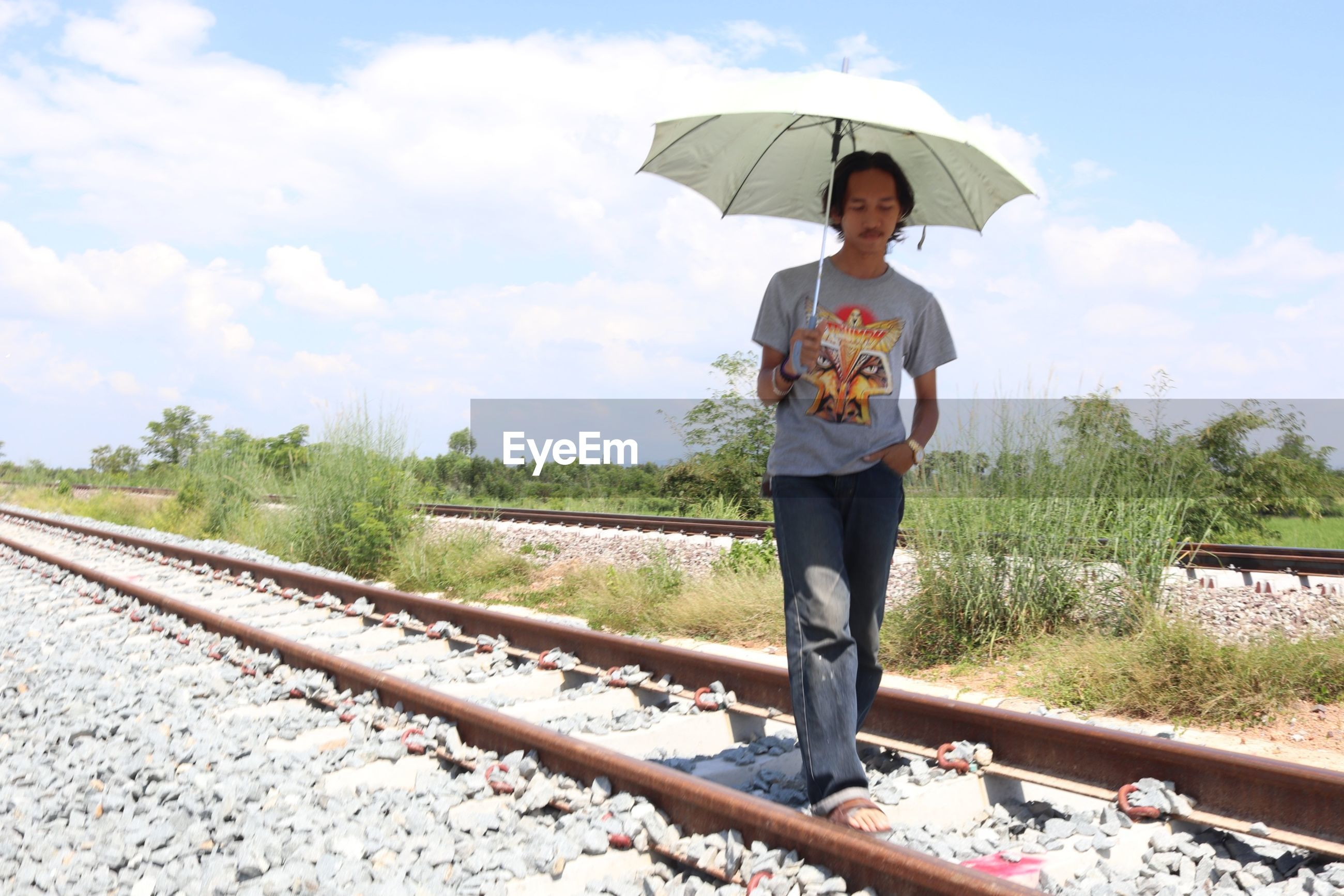 Man holding umbrella standing on railroad track against sky