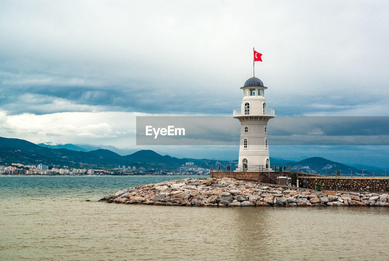 Turkish flag on lighthouse by sea against cloudy sky