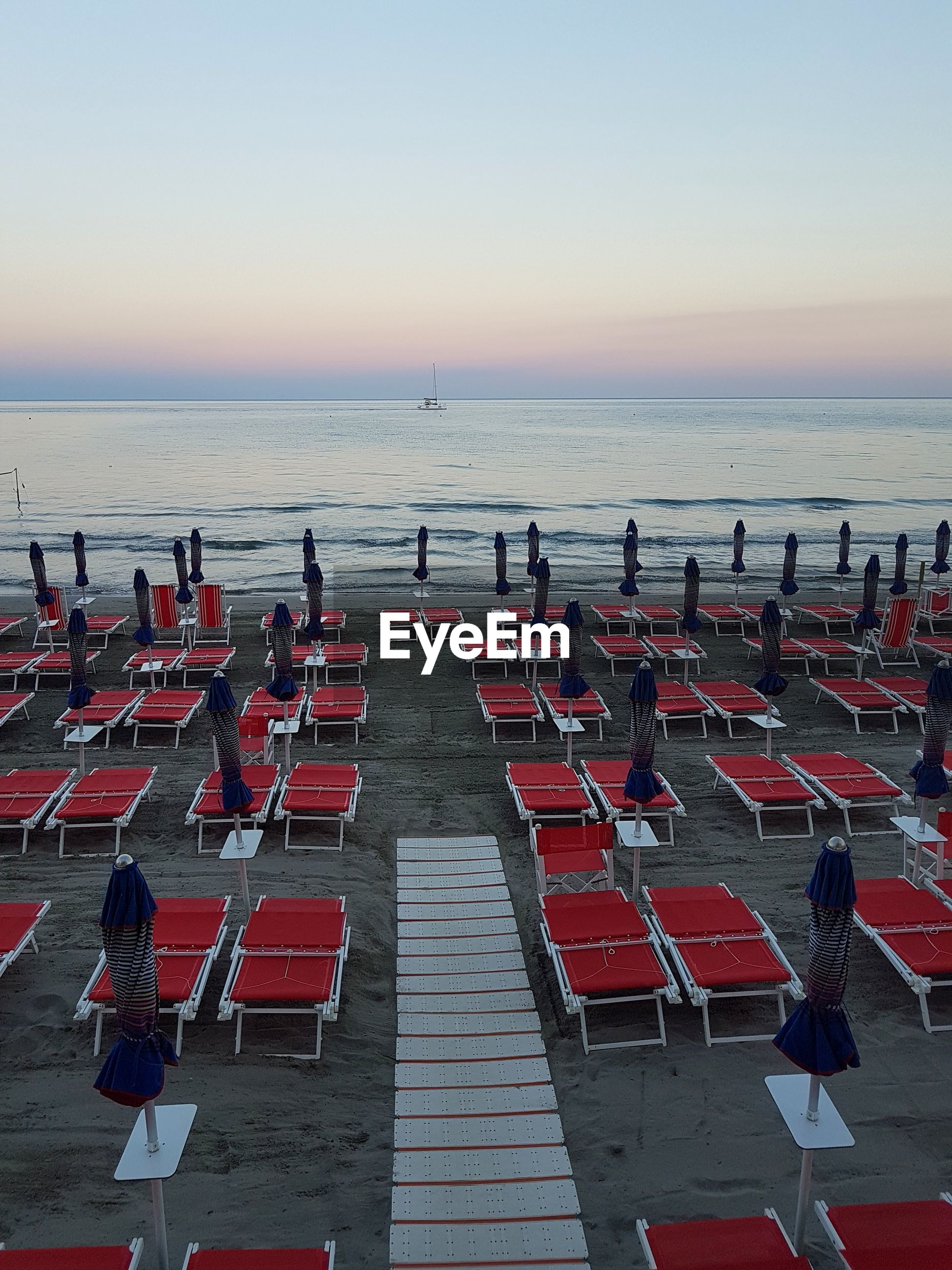 Empty lounge chairs at beach against clear sky during sunset