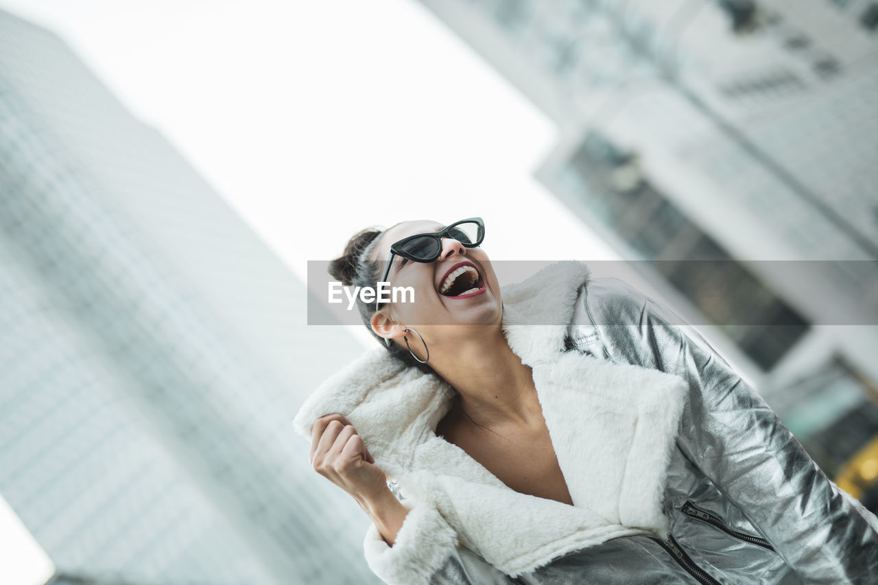 one person, lifestyles, leisure activity, young adult, glasses, real people, young women, architecture, women, adult, built structure, day, waist up, clothing, low angle view, fashion, focus on foreground, sunglasses, beautiful woman, outdoors