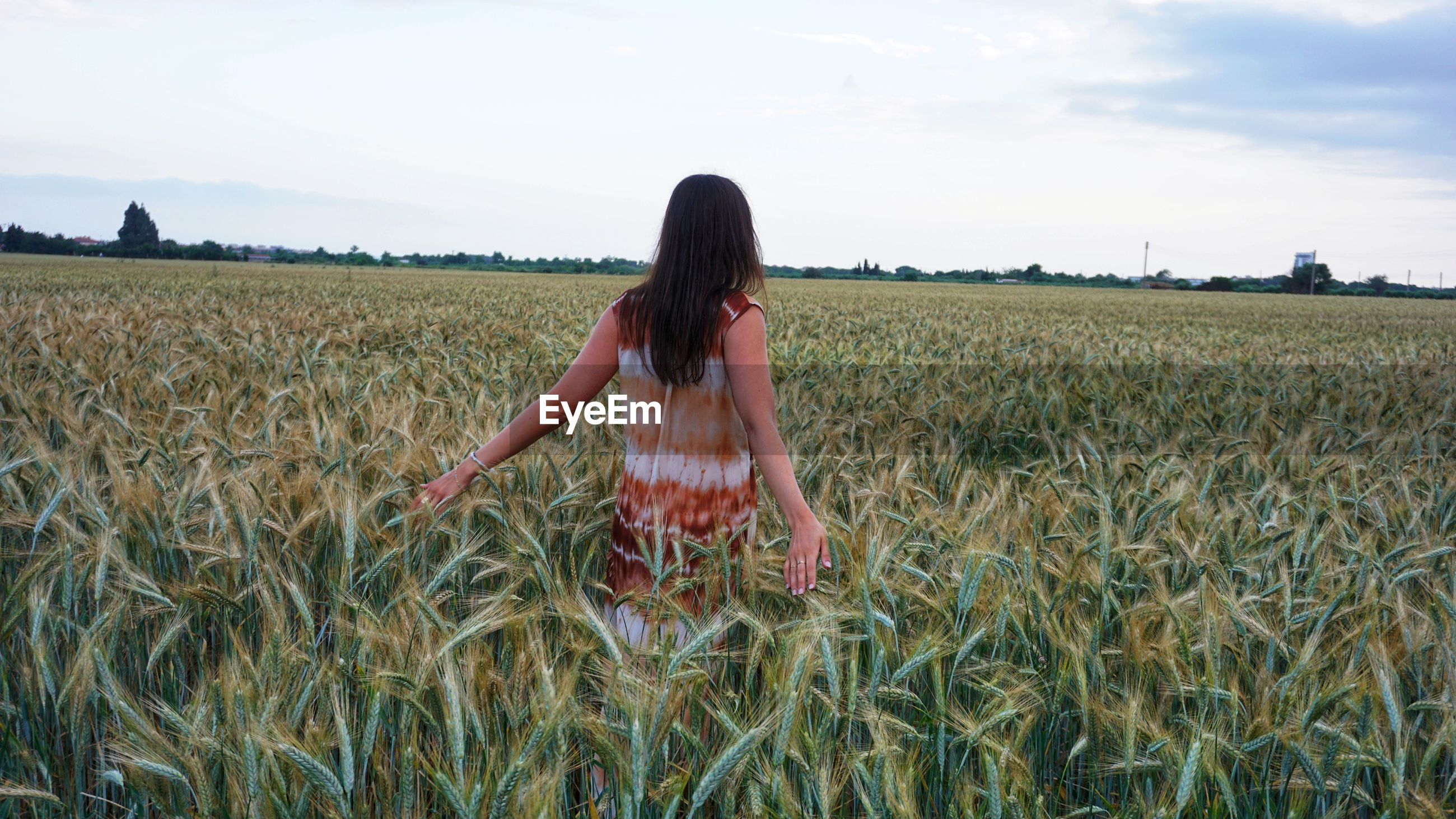 Woman standing in farm against sky