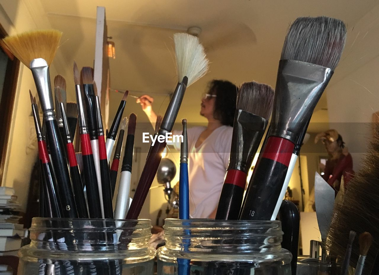 Close-Up Of Paintbrushes Against Artist Painting At Home