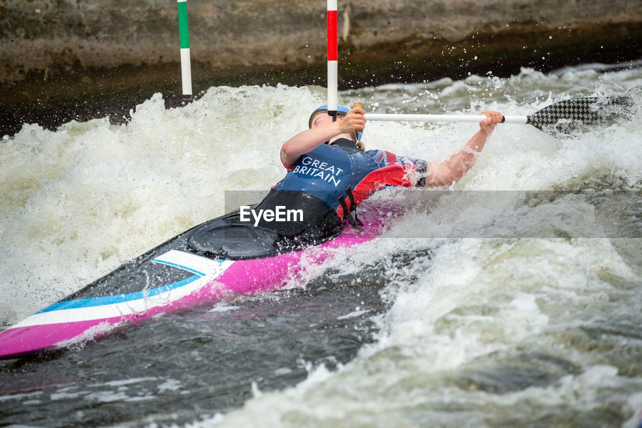 Gb canoe slalom athlete ducking under slalom pole while negotiating upstream gate in white water.
