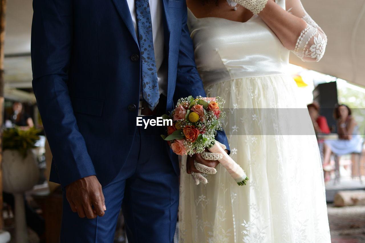 Midsection Of Couple Holding Flower Bouquet During Wedding