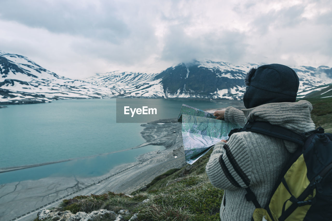 Woman With Map Standing At Lakeshore Against Mountains During Winter
