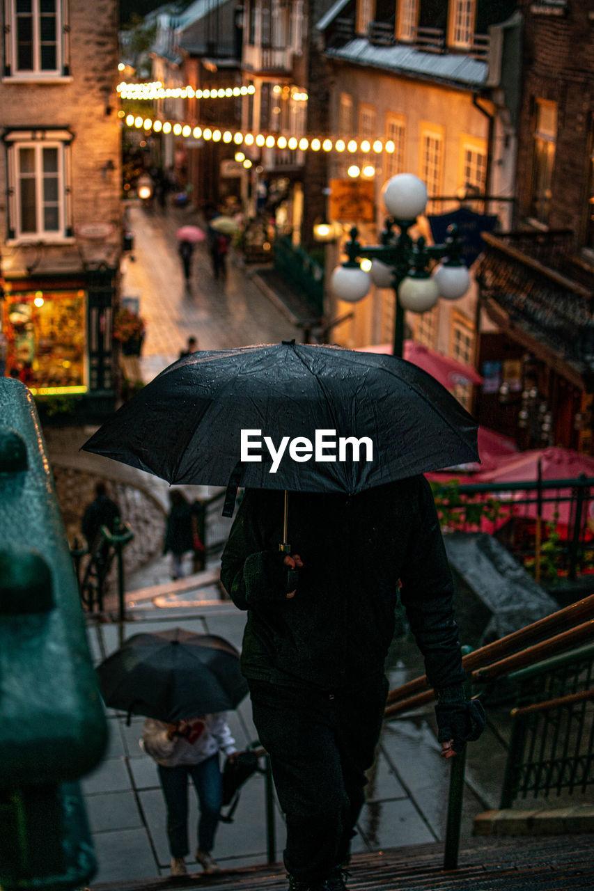 Man with umbrella walking in city during rainy season