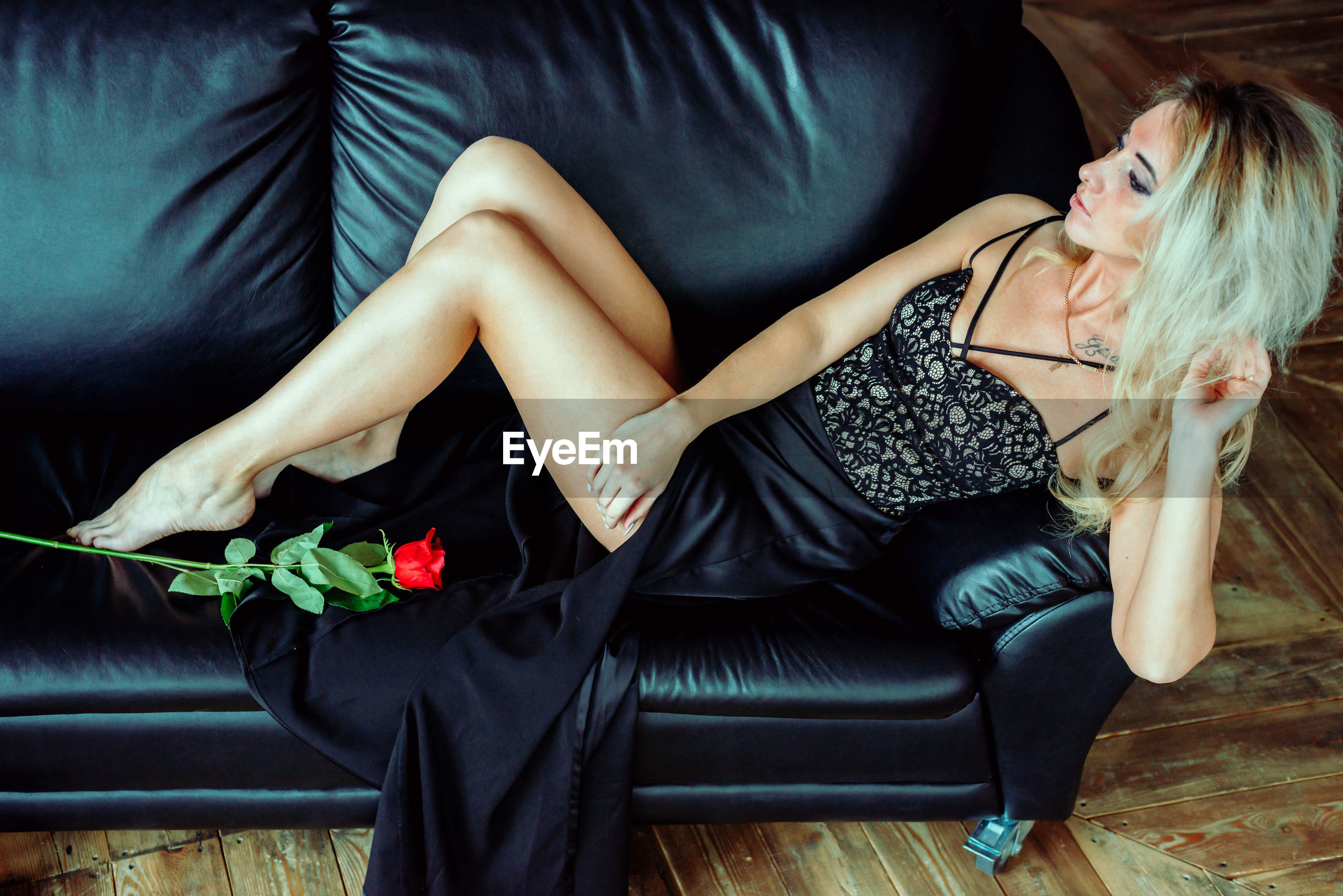 Sensuous woman with rose leaning on sofa at home