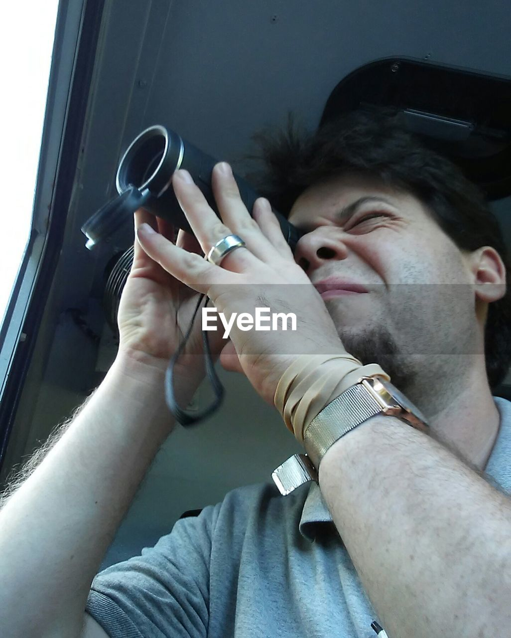 Close-up of man photographing through window