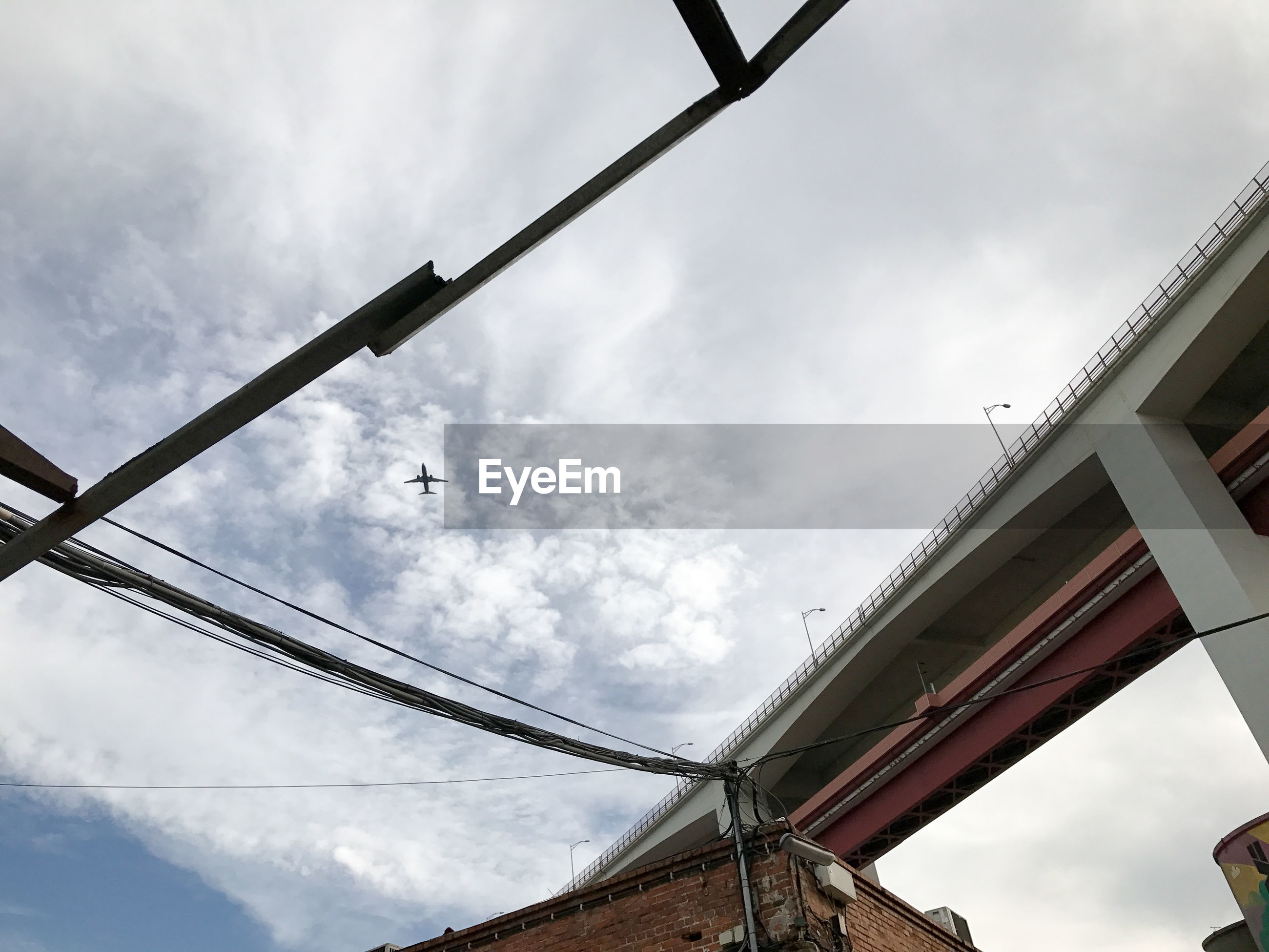 low angle view, sky, cloud - sky, no people, nature, built structure, day, architecture, outdoors, metal, connection, bridge - man made structure, building exterior, bridge, transportation, cable, protection, sunlight, lighting equipment, power supply