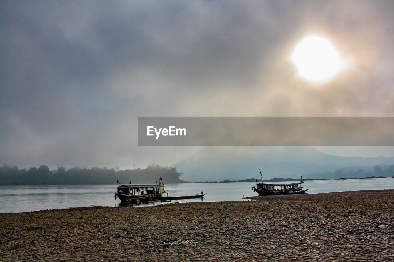 sky, nautical vessel, water, cloud - sky, transportation, mode of transportation, sea, scenics - nature, beauty in nature, land, tranquility, beach, nature, tranquil scene, moored, no people, horizon, non-urban scene, outdoors, horizon over water, fishing boat, low tide
