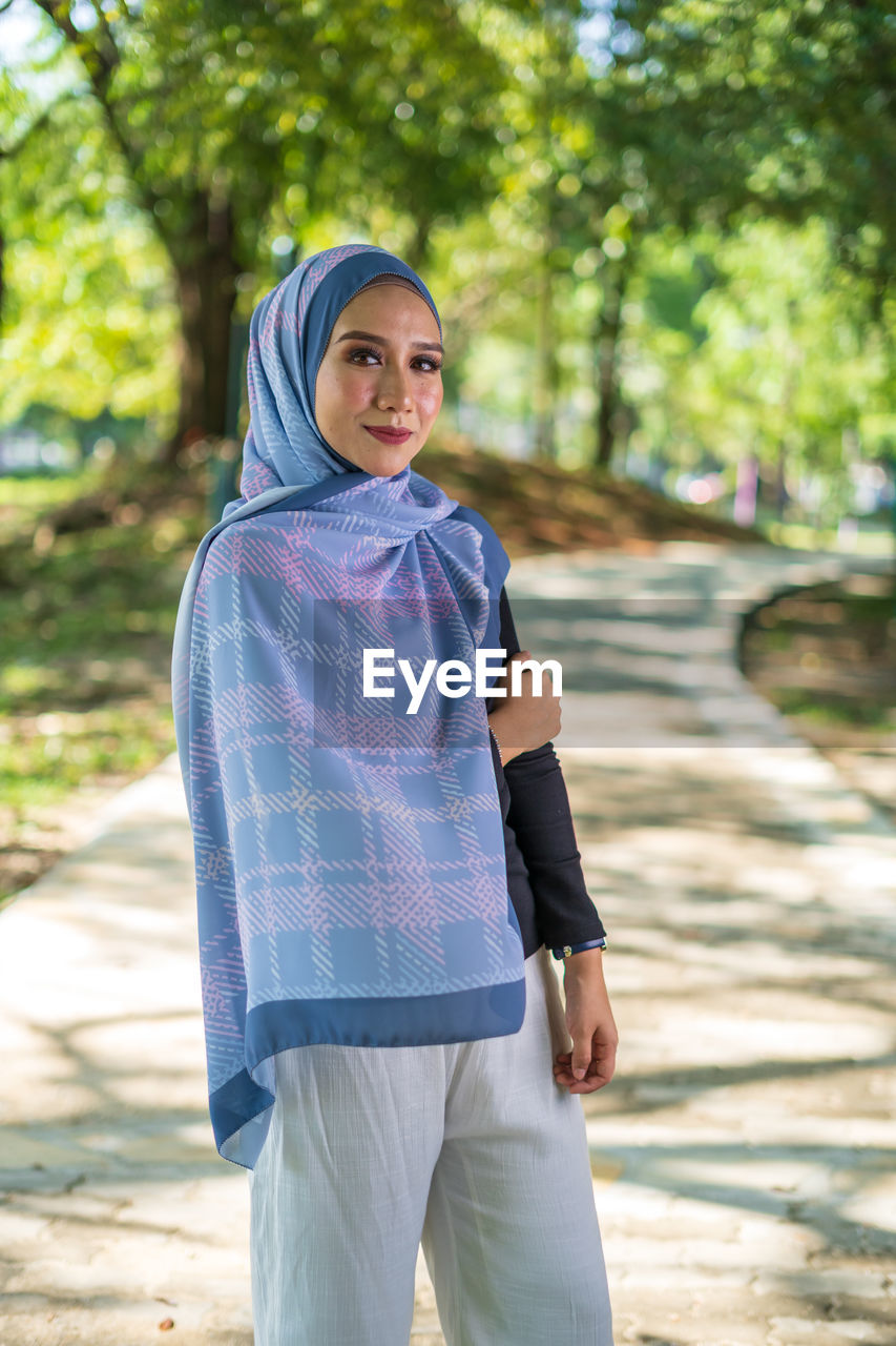 one person, looking at camera, focus on foreground, smiling, real people, portrait, day, tree, young adult, three quarter length, casual clothing, lifestyles, standing, leisure activity, young women, sunlight, front view, hijab, outdoors, teenager