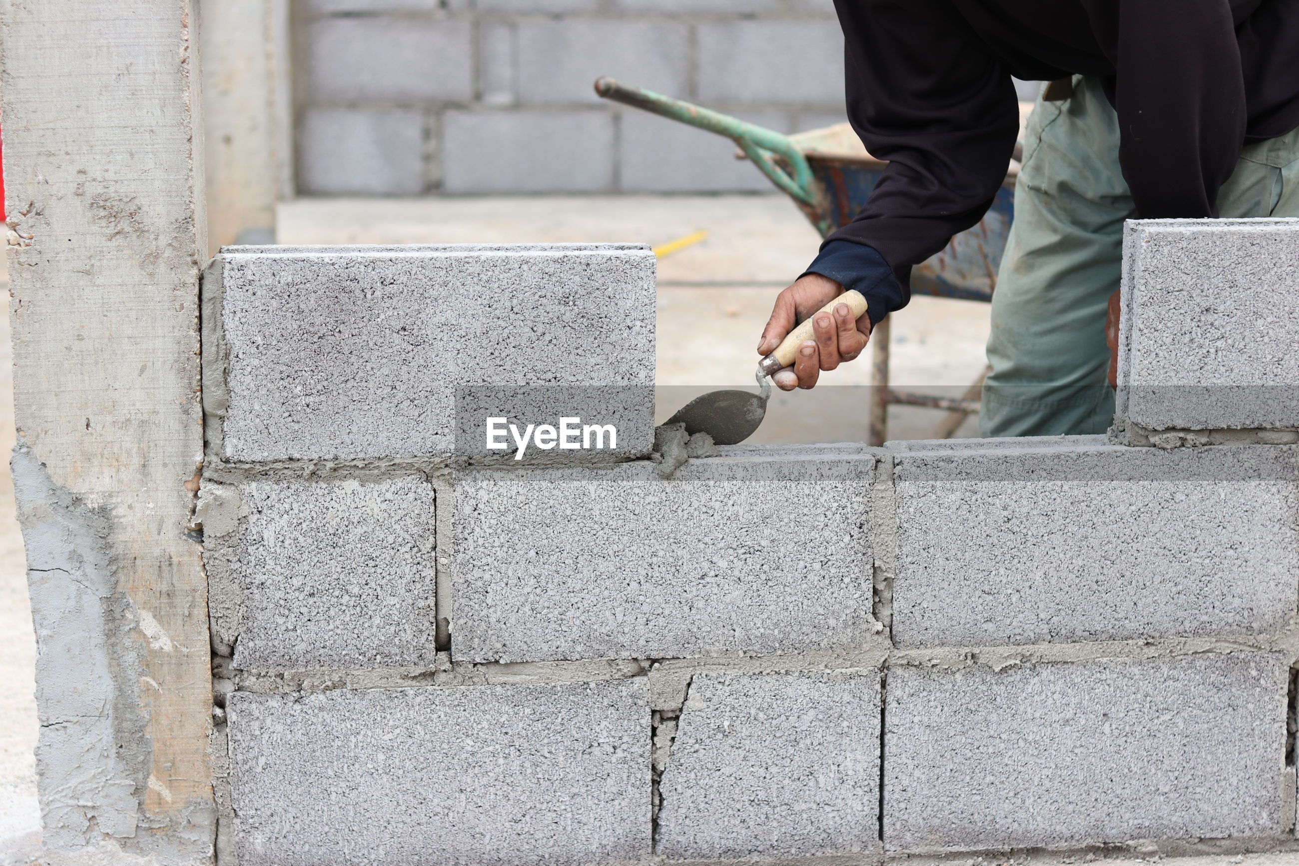 Midsection of construction worker making concrete wall