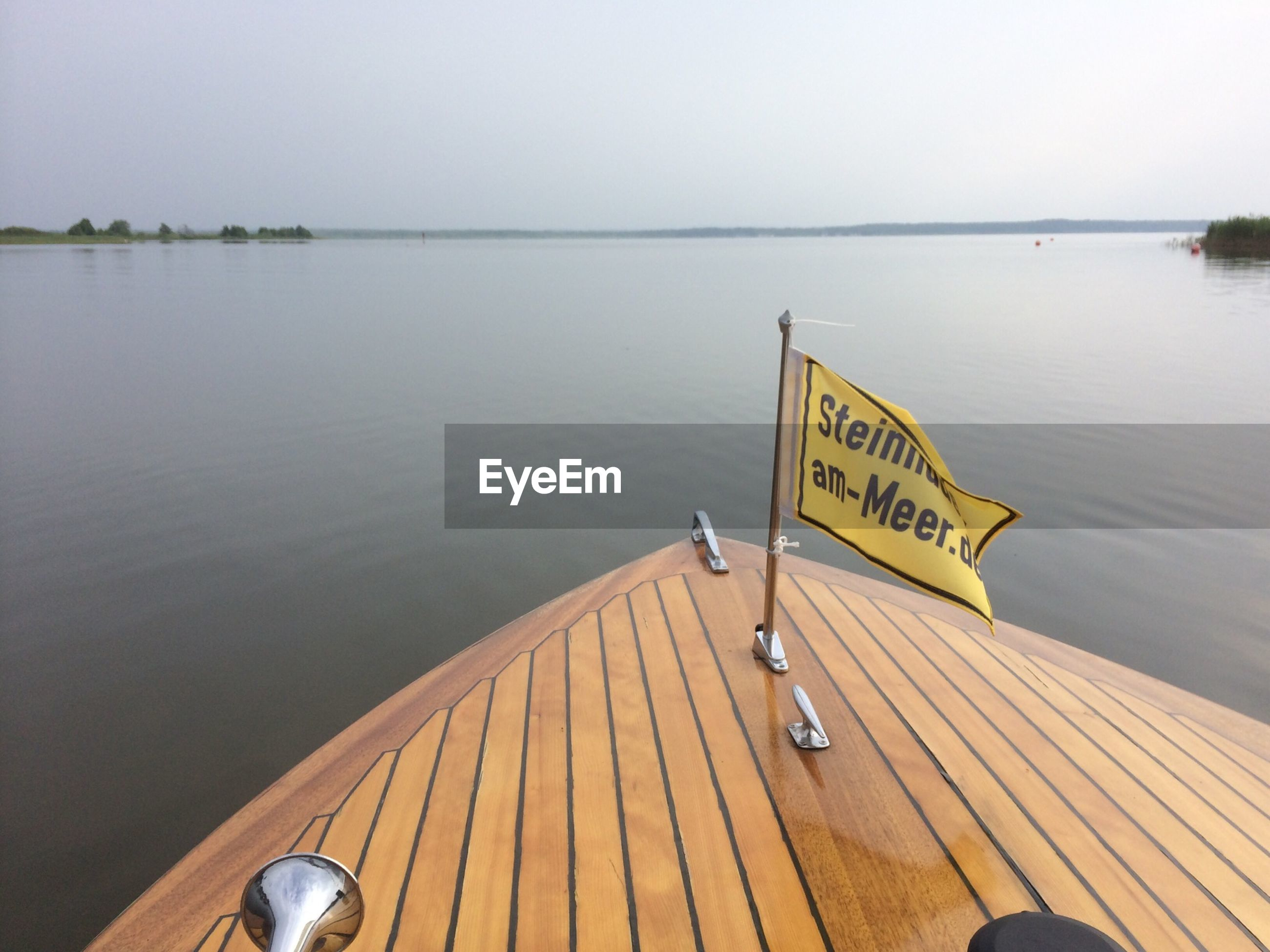 water, text, western script, sea, pier, tranquil scene, tranquility, wood - material, communication, horizon over water, sky, nature, scenics, sign, information sign, nautical vessel, lake, beauty in nature, boat, transportation