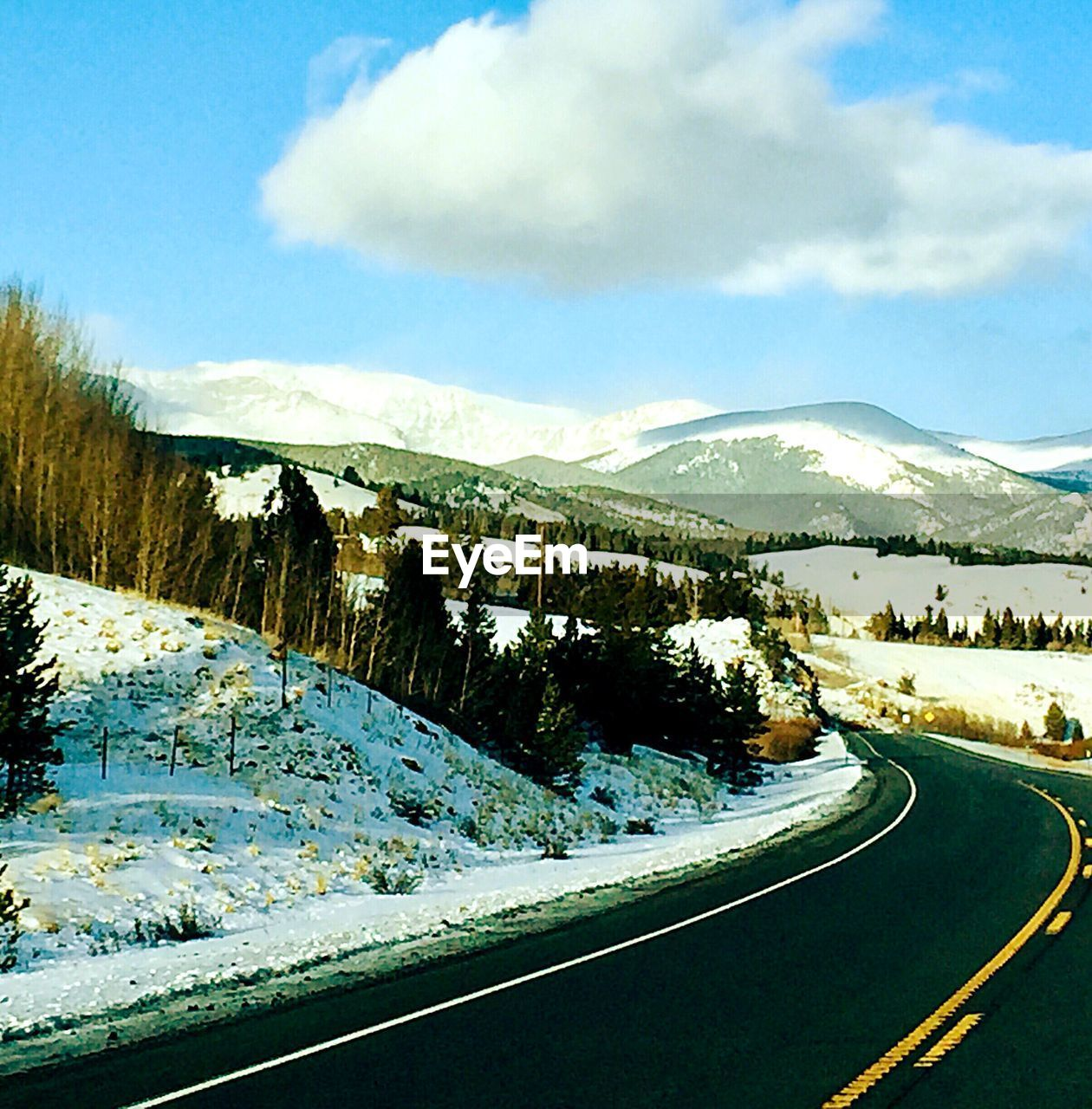 mountain, sky, road, cloud - sky, winter, snow, scenics - nature, transportation, beauty in nature, cold temperature, day, nature, tranquility, tranquil scene, mountain range, no people, environment, non-urban scene, tree, winding road, snowcapped mountain, outdoors