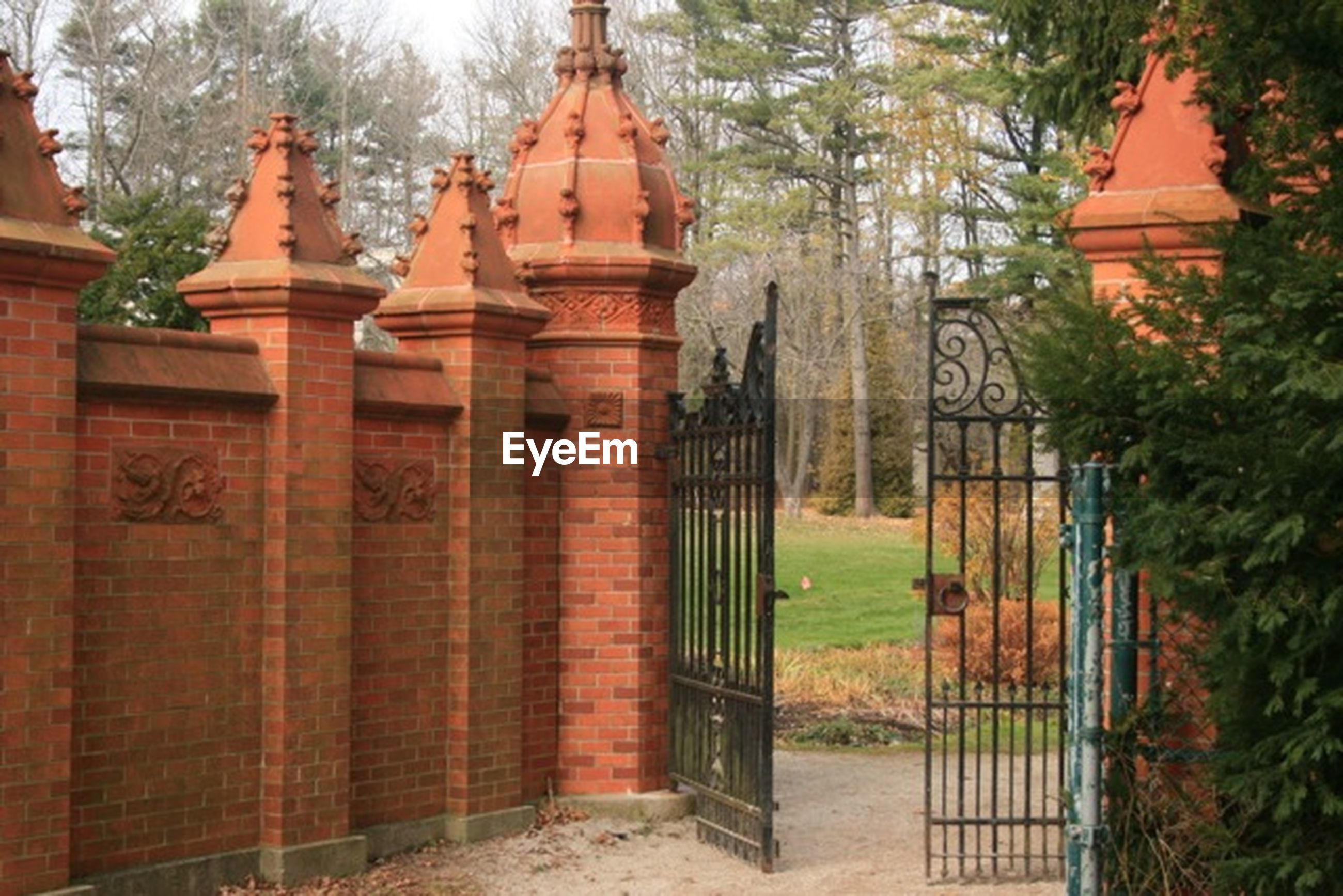 built structure, architecture, building exterior, tree, gate, entrance, door, closed, day, old, house, no people, outdoors, safety, protection, architectural column, wood - material, religion, fence, wall - building feature