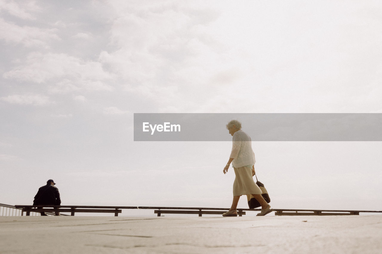 Side View Of Woman Walking On Footpath Against Sky During Sunny Day