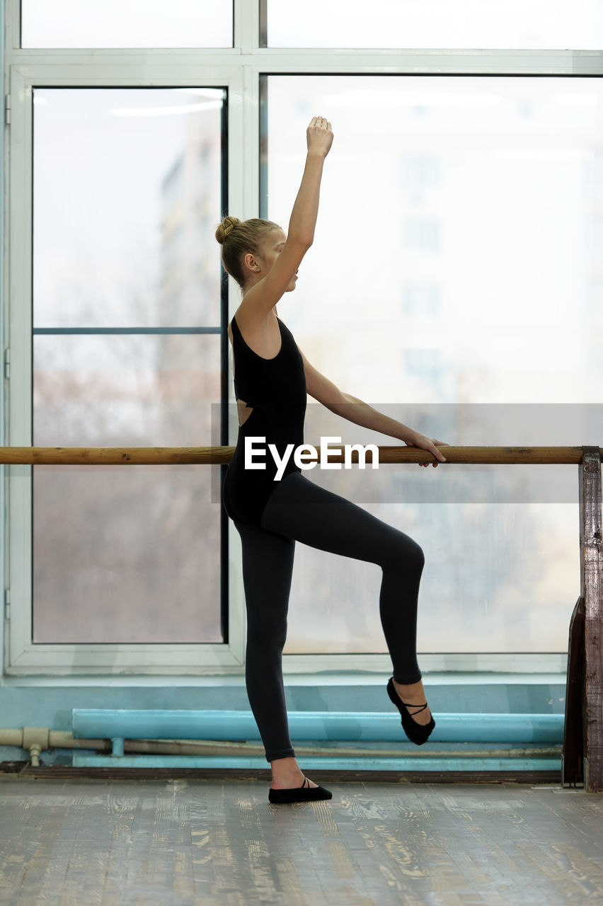 one person, lifestyles, full length, exercising, ballet, dancing, indoors, flexibility, ballet dancer, real people, skill, healthy lifestyle, women, balance, stretching, standing, window, practicing, leisure activity, arms raised, human arm, flooring
