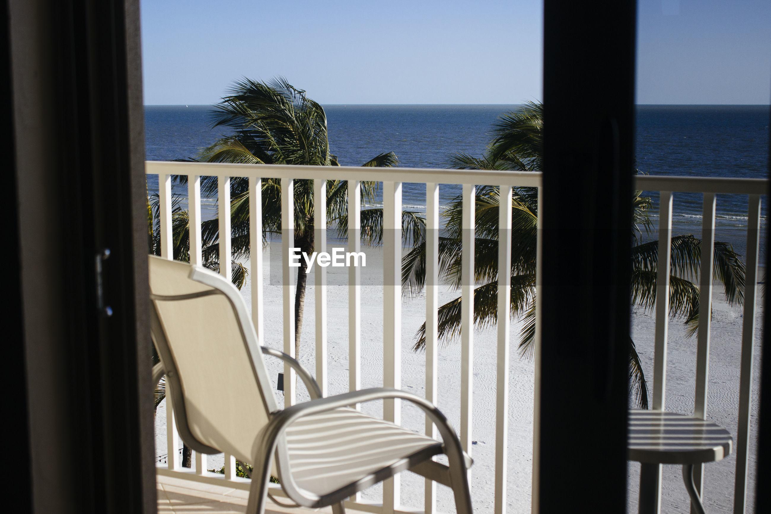 Empty chair on balcony by sea against sky