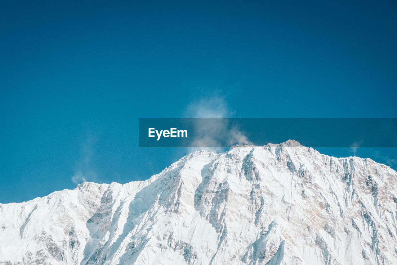 SNOWCAPPED MOUNTAINS AGAINST BLUE SKY