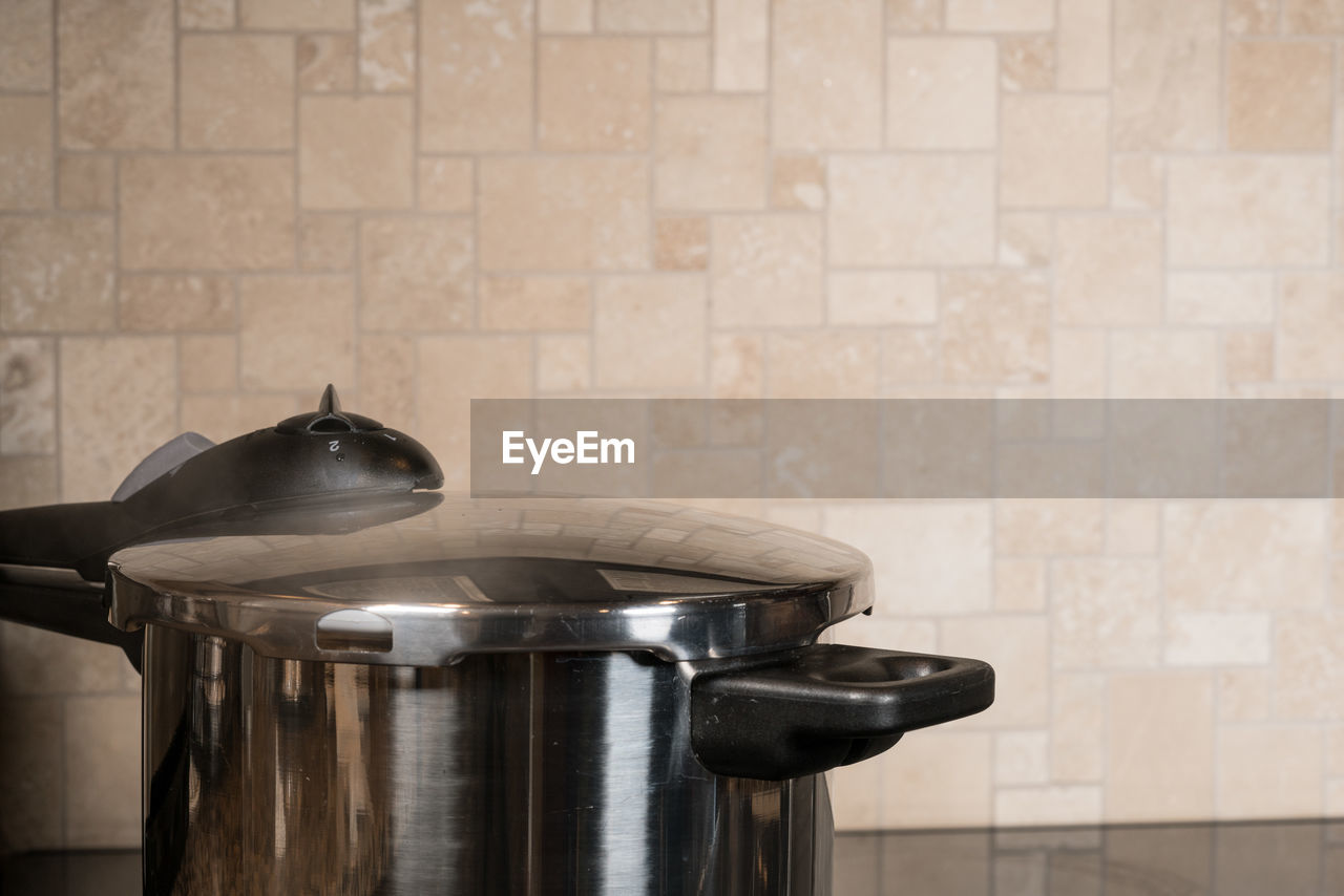 indoors, wall - building feature, close-up, no people, tile, domestic room, metal, flooring, home, kitchen utensil, container, domestic kitchen, household equipment, kitchen, cooking pan, shiny, still life, preparation, steel, musical instrument, silver colored, saucepan