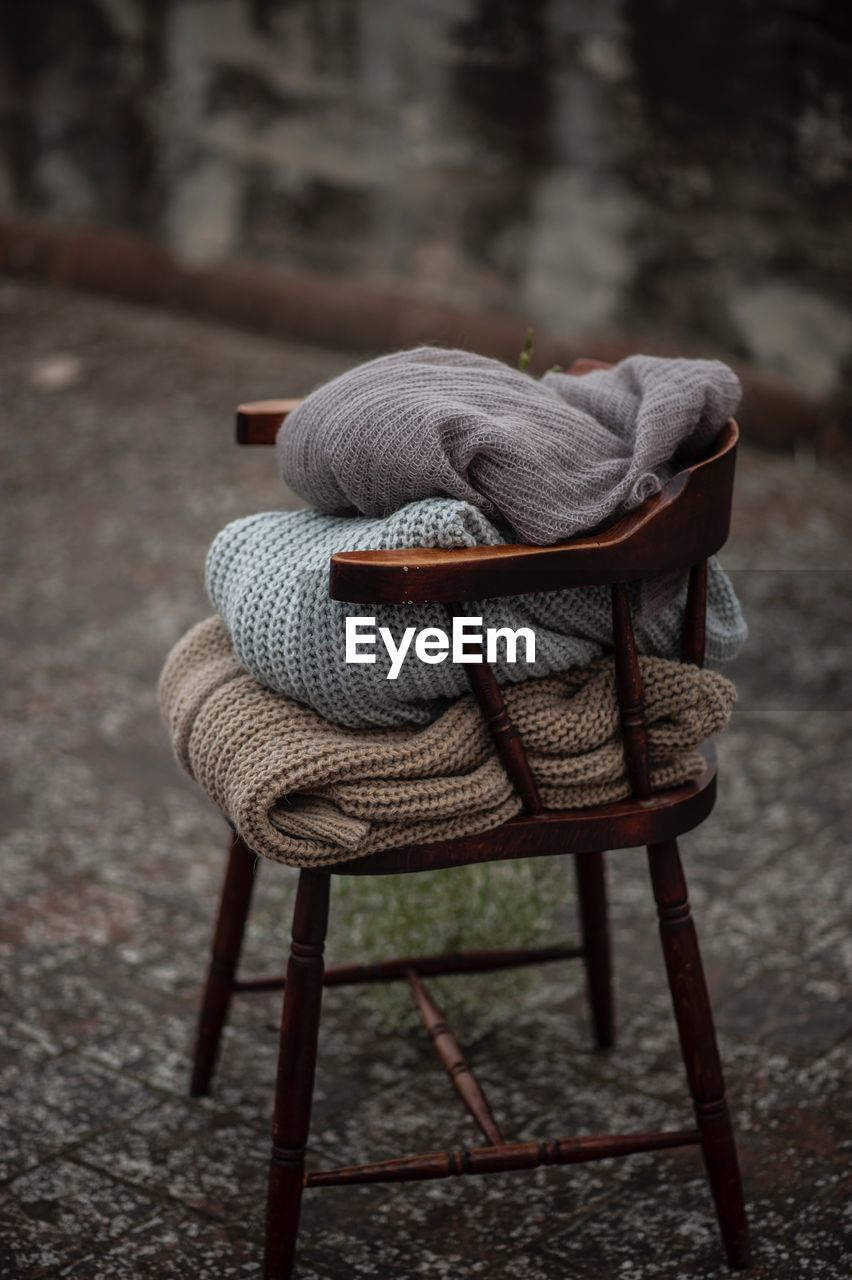 seat, chair, no people, focus on foreground, absence, day, hat, still life, wood - material, outdoors, clothing, textile, close-up, craft, art and craft, street, furniture, relaxation, high angle view, footpath
