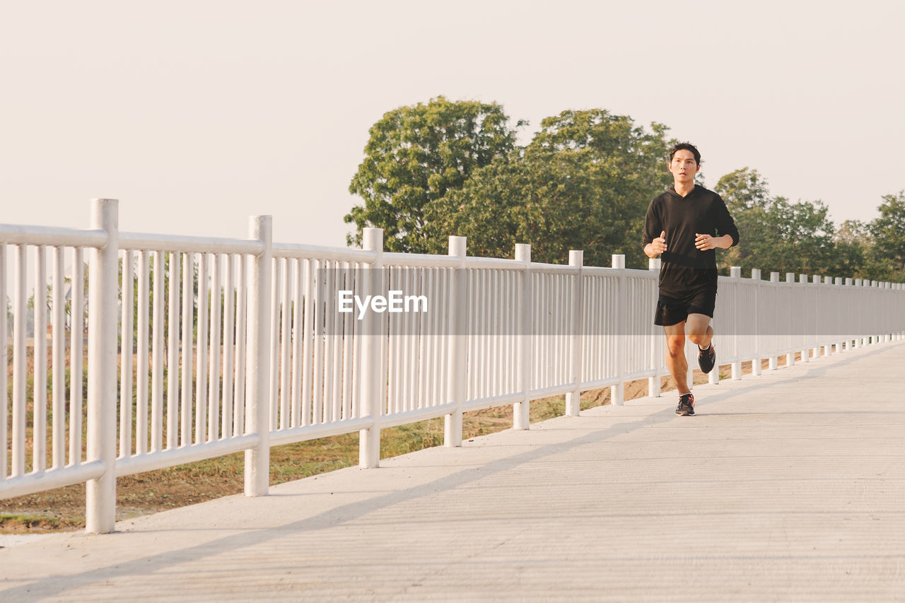 one person, lifestyles, full length, real people, leisure activity, young adult, casual clothing, railing, plant, nature, sky, young men, clear sky, front view, built structure, day, tree, footpath, outdoors, shorts