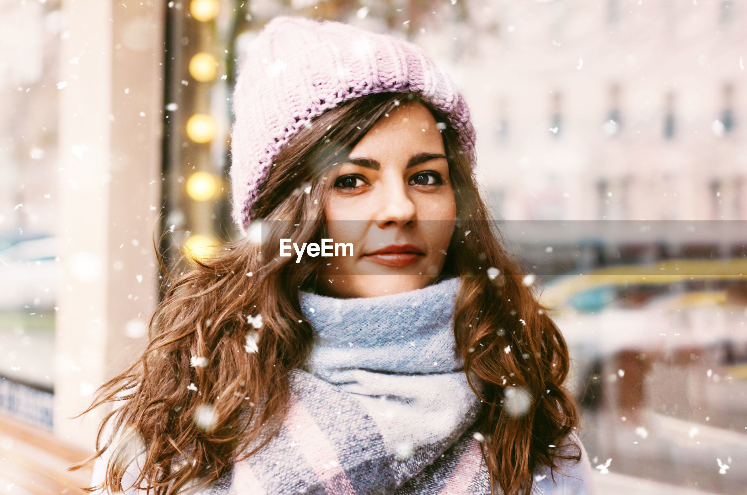 Portrait of young woman standing against building during snowfall