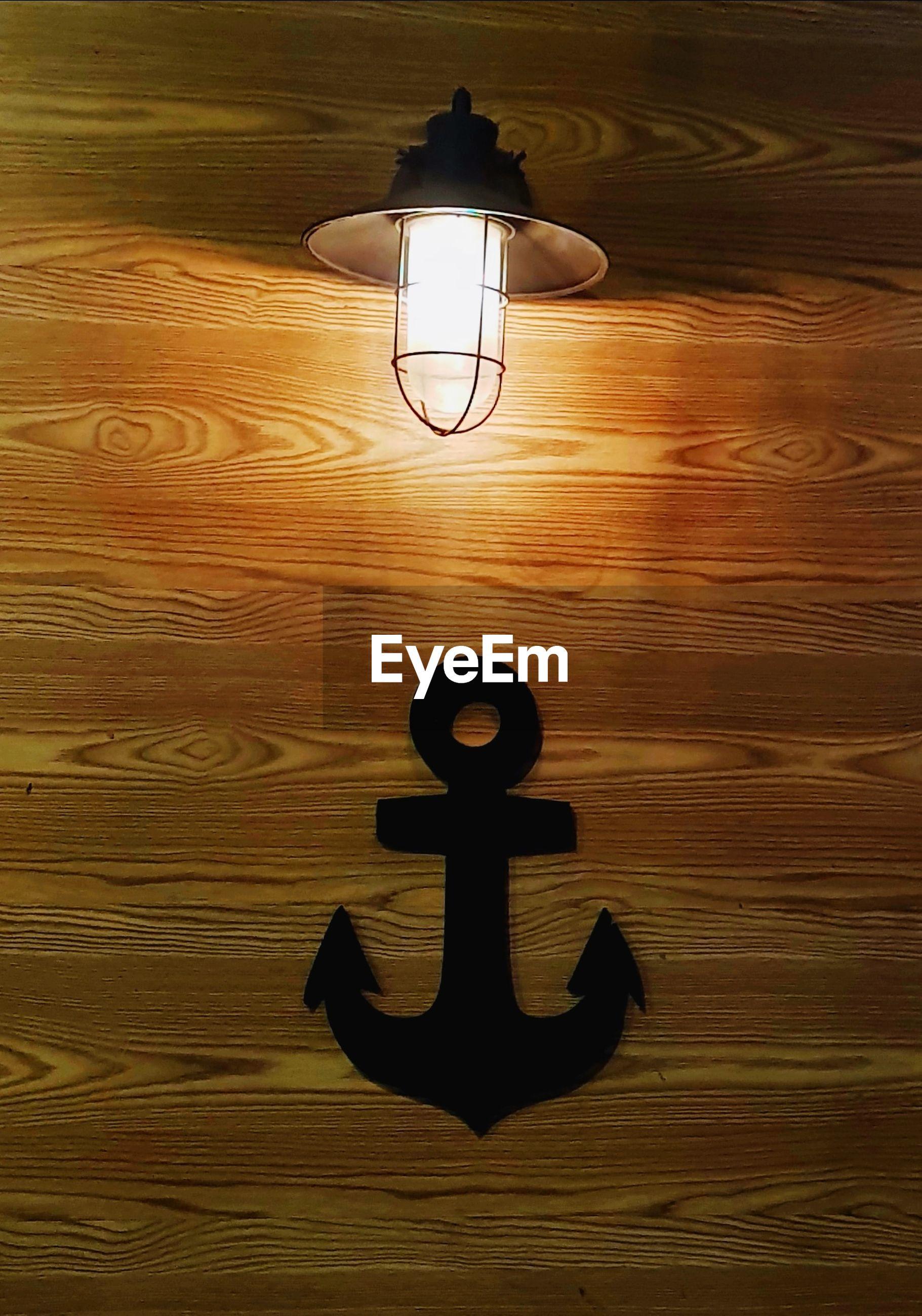Illuminated light bulb on wooden wall