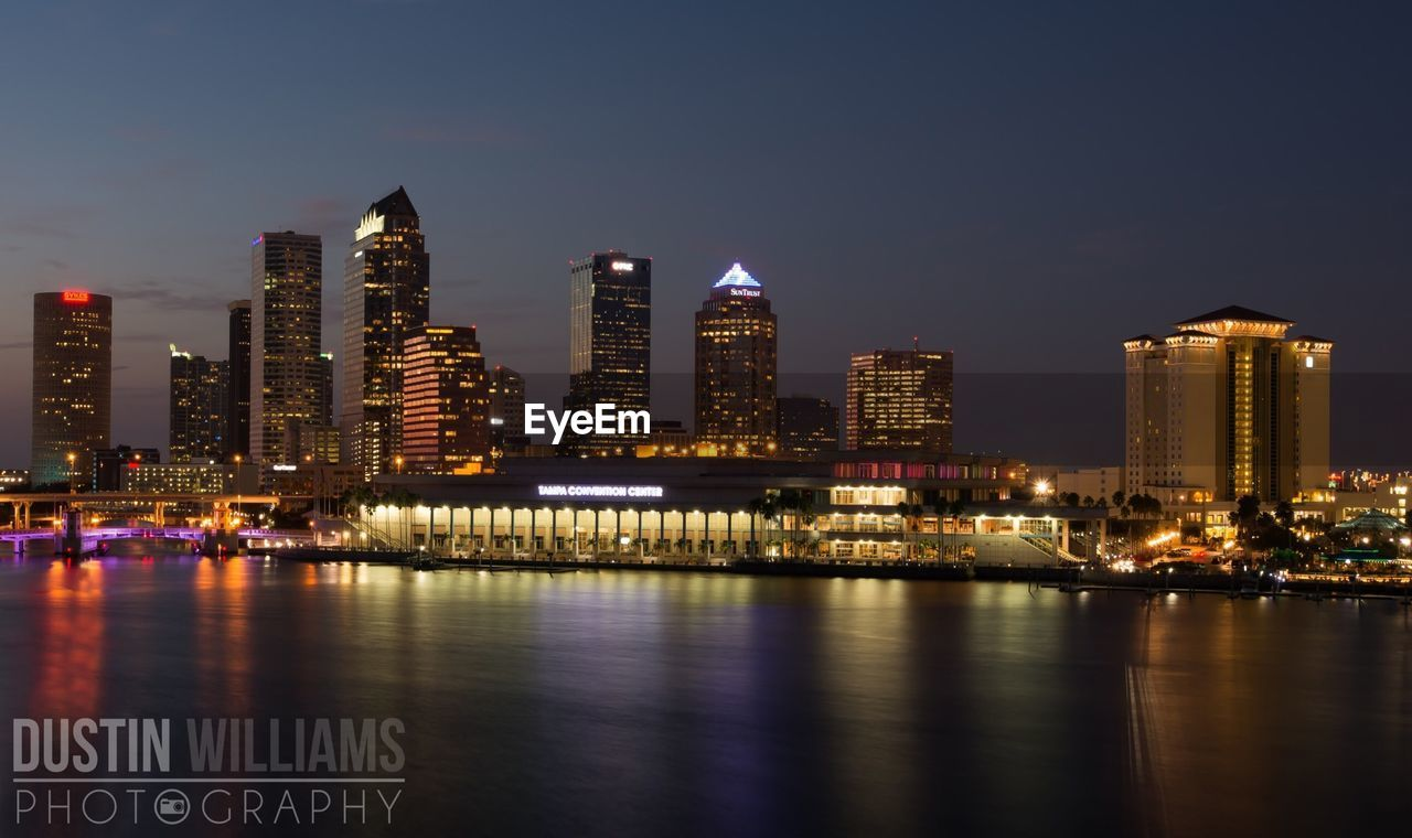 illuminated, building exterior, architecture, skyscraper, night, urban skyline, city, built structure, river, cityscape, waterfront, travel destinations, sky, water, outdoors, no people, modern